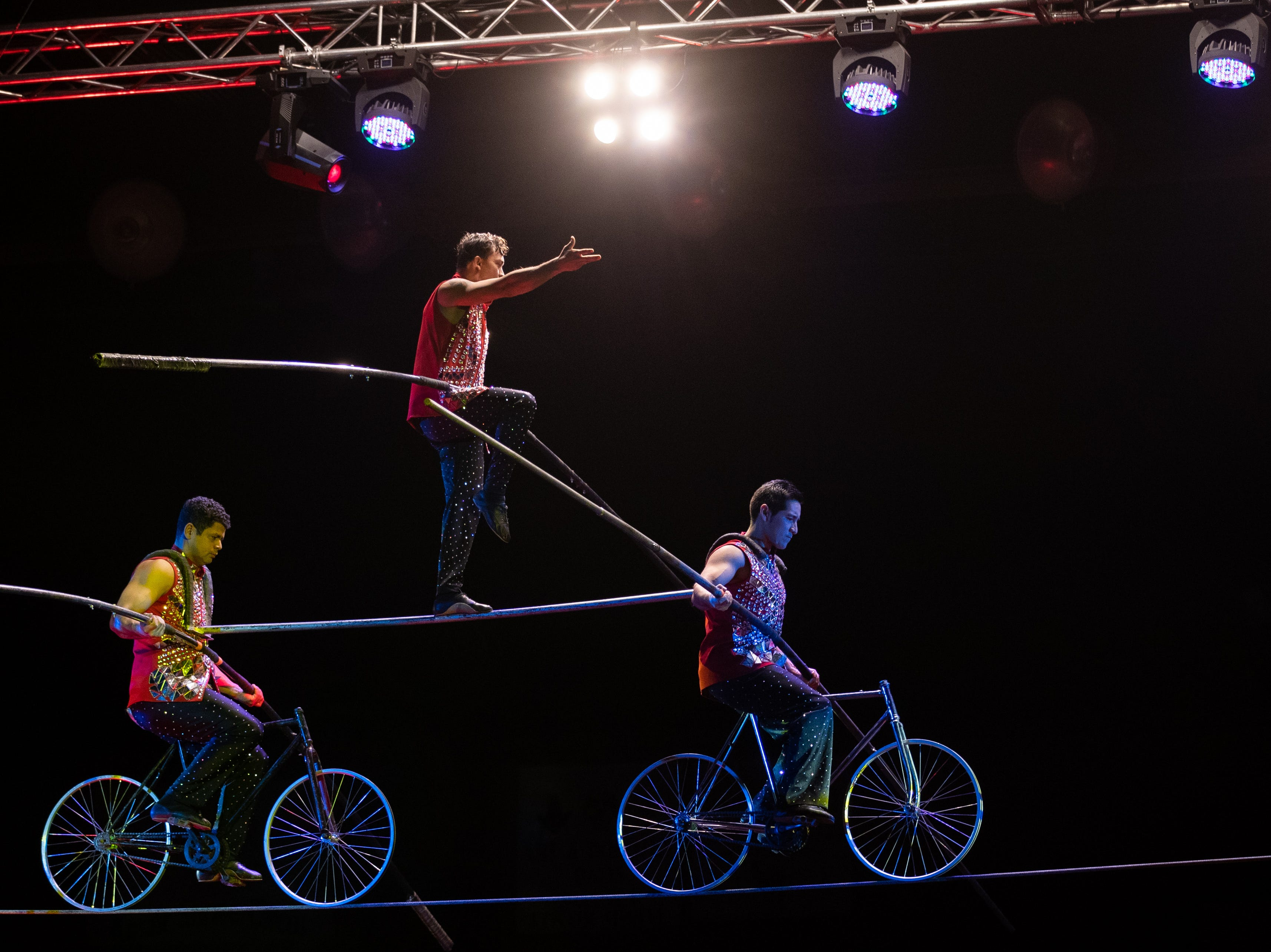 """Three tightrope performers balance on two bikes, a move touted """"the human pyramid"""" by the ringmaster, Saturday, Feb. 9, 2019 in Louisville Ky."""