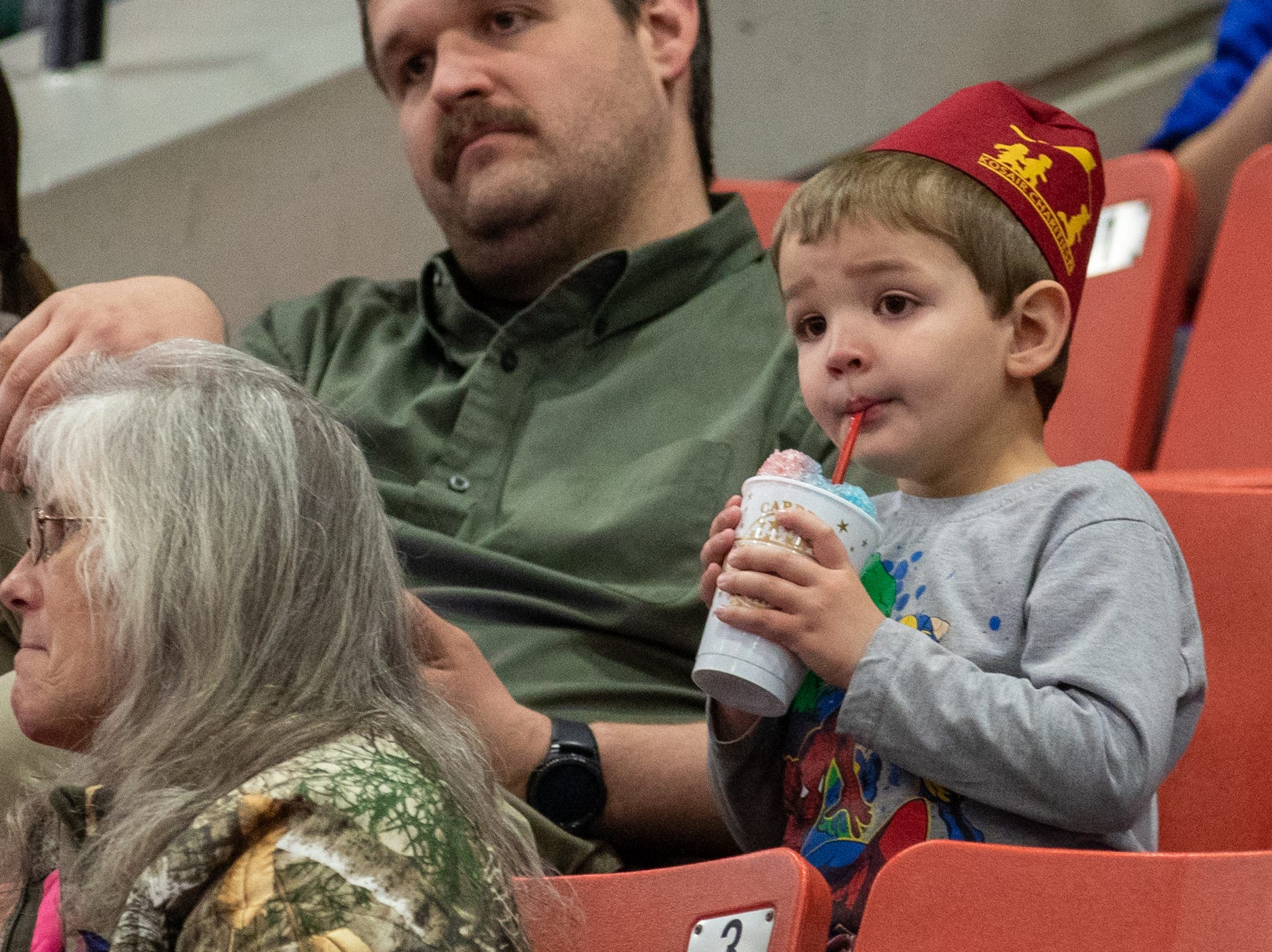 Slurping a shaved ice drink, a young spectator waits anxiously for the circus to begin, Saturday, Feb. 9, 2019 in Louisville Ky.