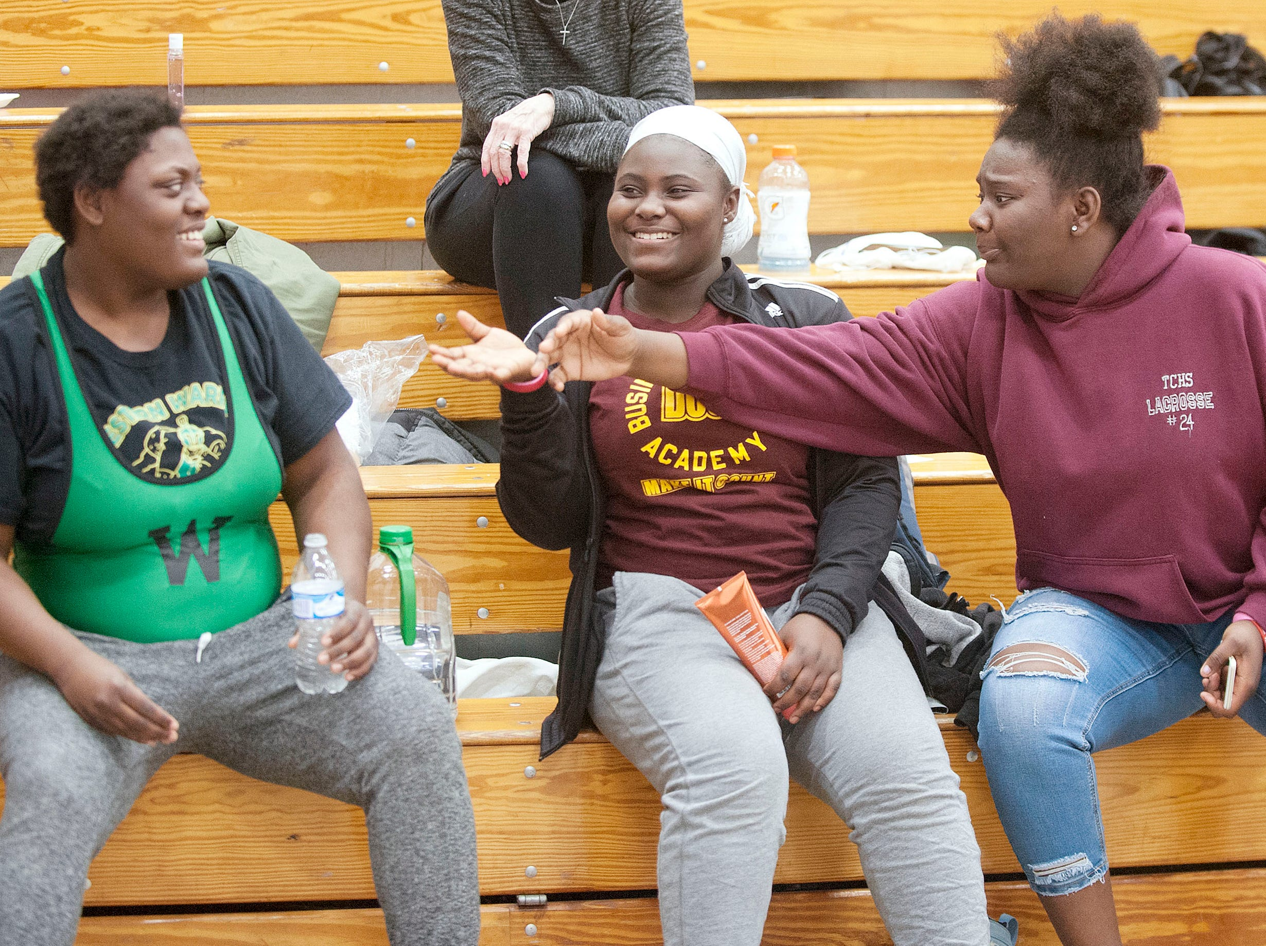 Western wrestler Malasha Lokey, left,  jokes with two of her close friends, Angel Badu, a former Western student now at Doss, center, and Karilya Sweet, right, Western's wrestling team manager.  The three were at a KHSAA Region 3 wrestling meet at Doss.09 February 2019