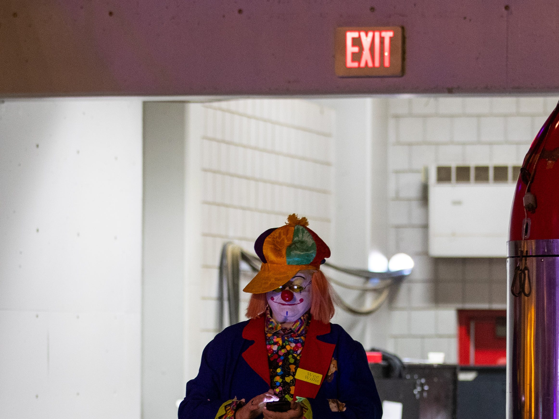 Clown performer takes a break on his cell phone during the second half of the Kosair Shrine Circus, Saturday, Feb. 9, 2019 in Louisville Ky.