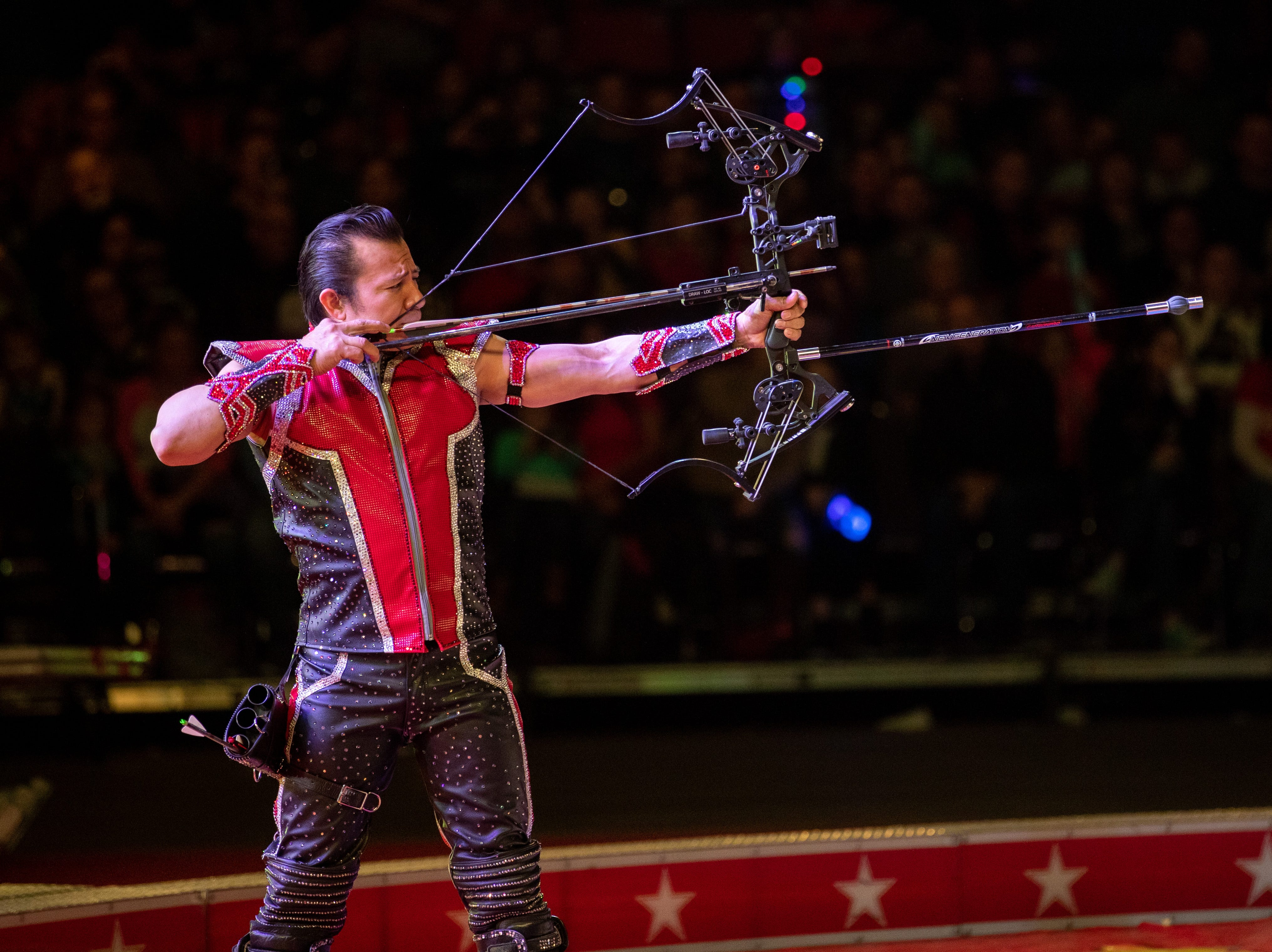 An archer trains his bow on an apple placed just above his assistant's head, Saturday, Feb. 9, 2019 in Louisville Ky.