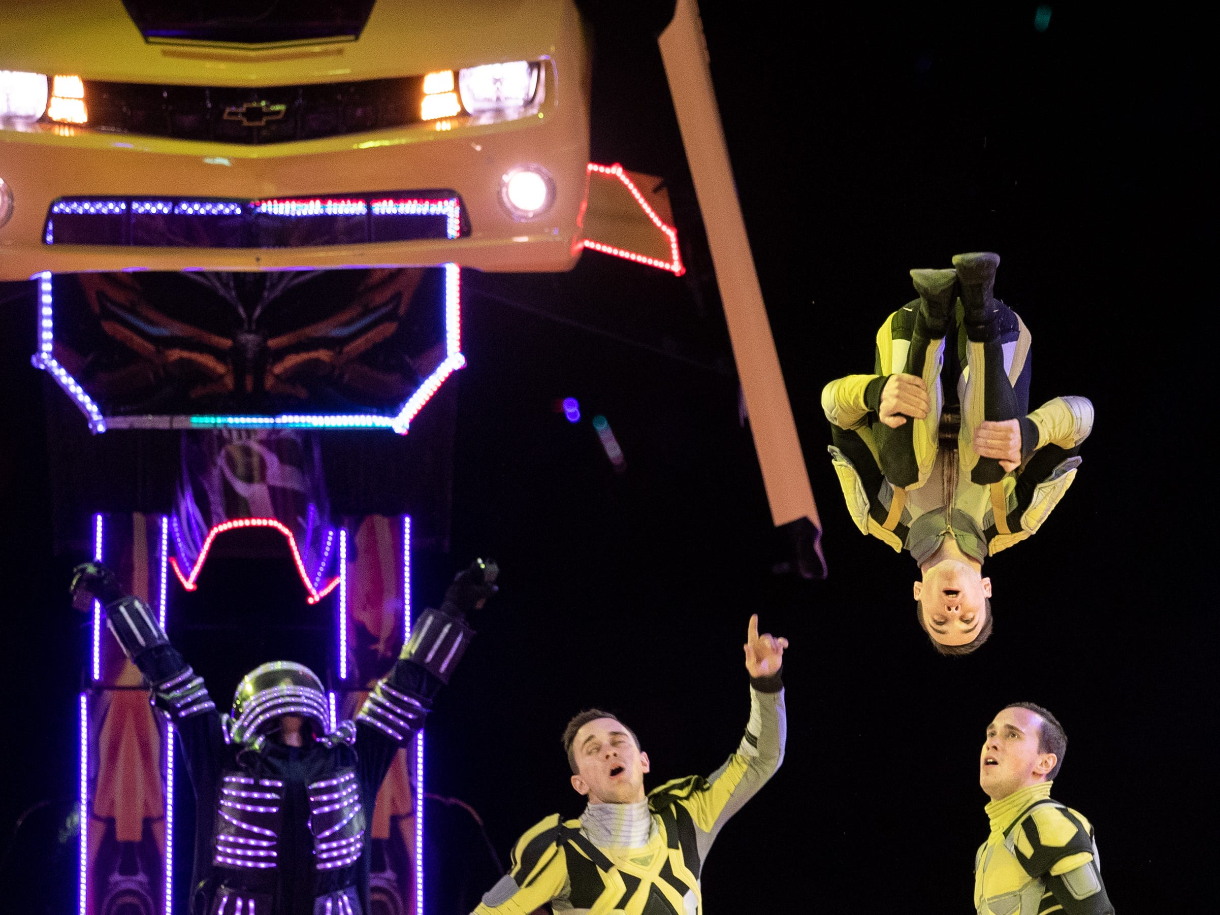 Floating like a bumblebee, a performer flips high in the air as Bumblebee, the Transformer, stands tall in the background, Saturday, Feb. 9, 2019 in Louisville, Kentucky.