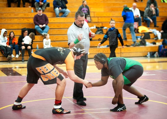 Fern Creek's Alex Martin, left, shakes hands with Malasha Lokey at the beginning of their contest.