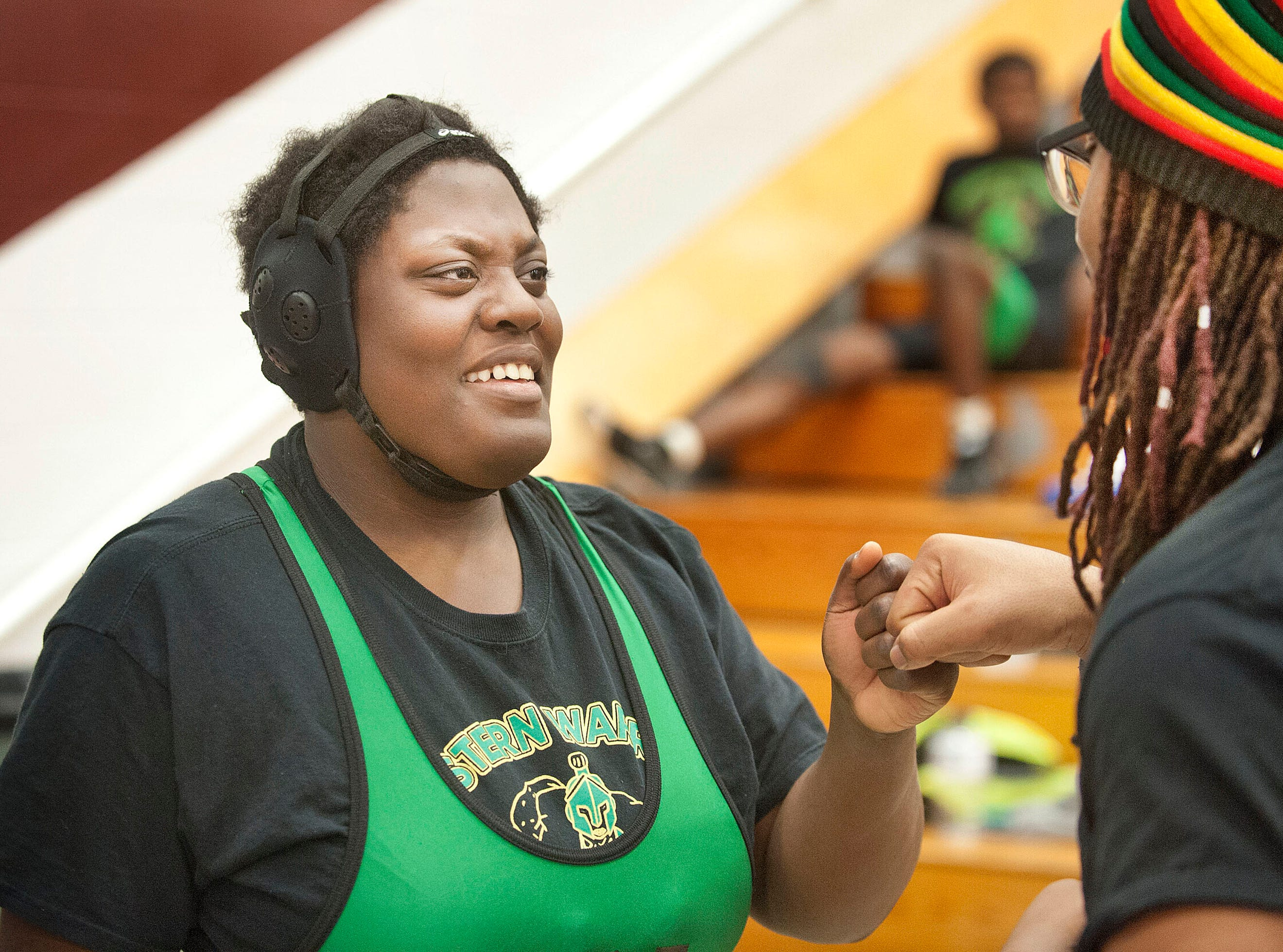 Assistant wrestling coach Desean Straaton gives her an encouraging fist bump before the start of her match.09 February 2019
