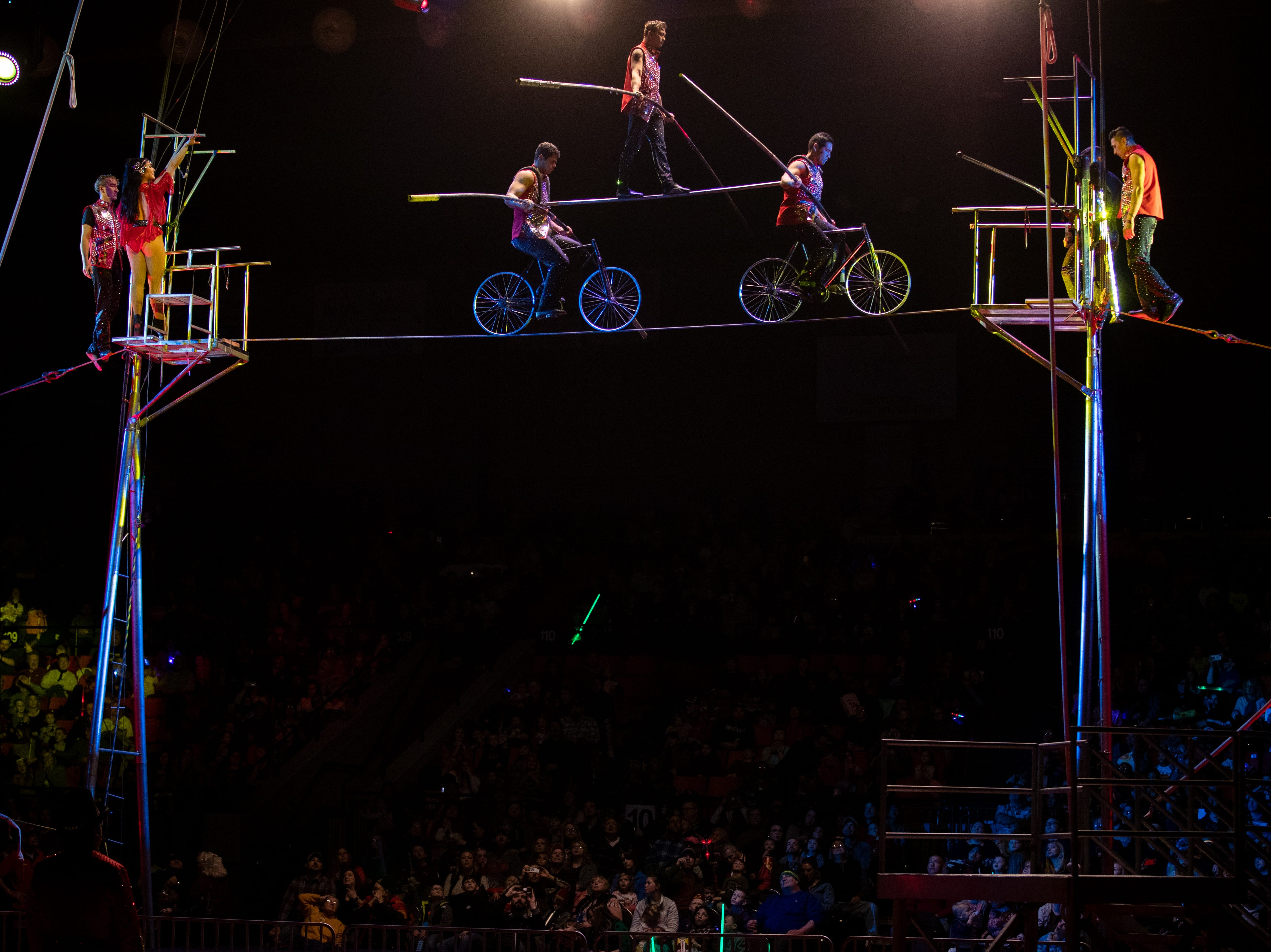 """High above the Broadbent Arena floor, three tightrope performers balance on two bikes, a move touted """"the human pyramid"""" by the ringmaster, Saturday, Feb. 9, 2019 in Louisville Ky."""