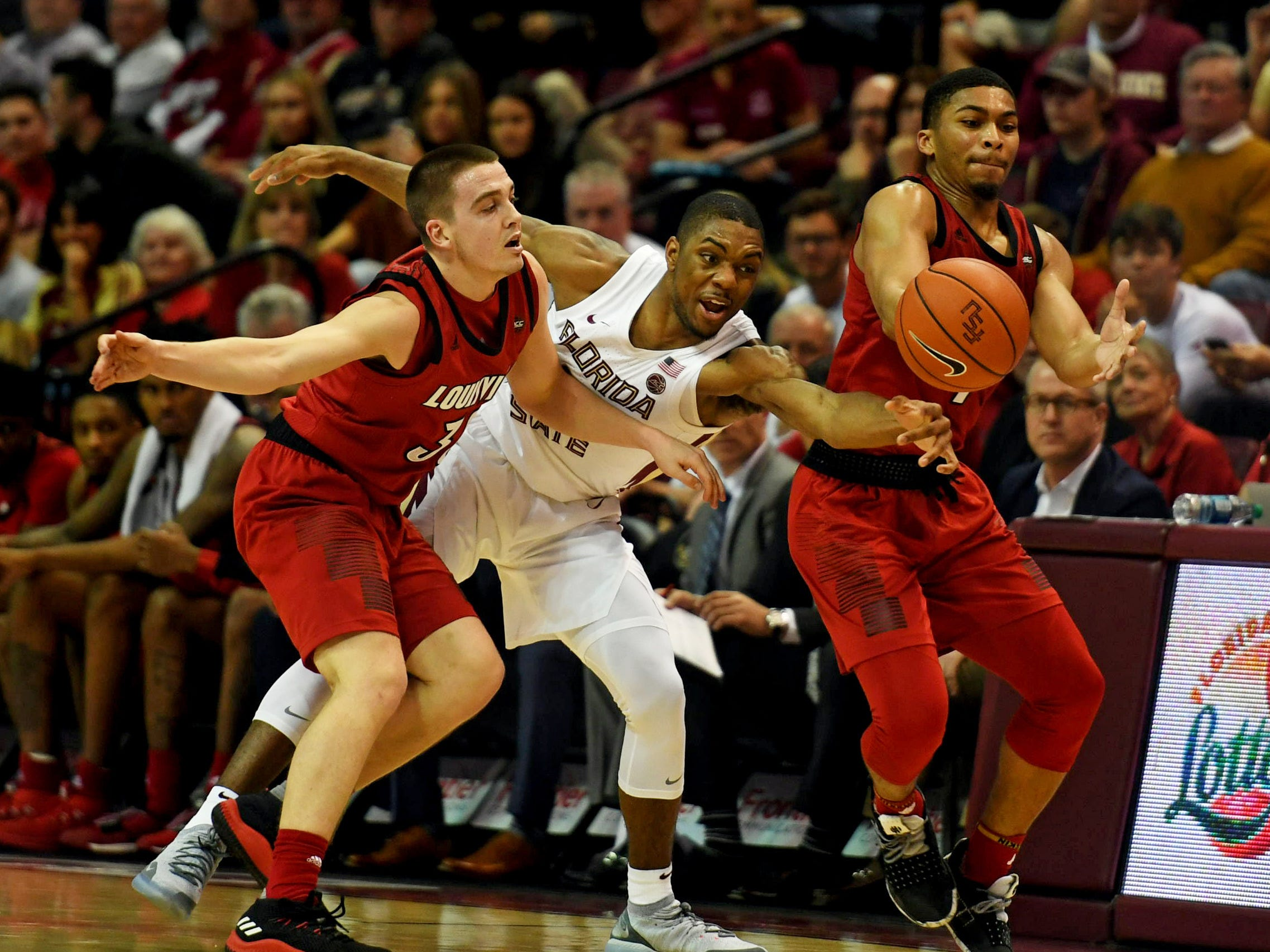 Louisville Cardinals guard Ryan McMahon (30) and guard Christen Cunningham (1) have the ball knocked away by Florida State Seminoles guard Trent Forrest (3) during the second half at Donald L. Tucker Center in Tallahassee, Florida, on Saturday, Feb. 9, 2019.