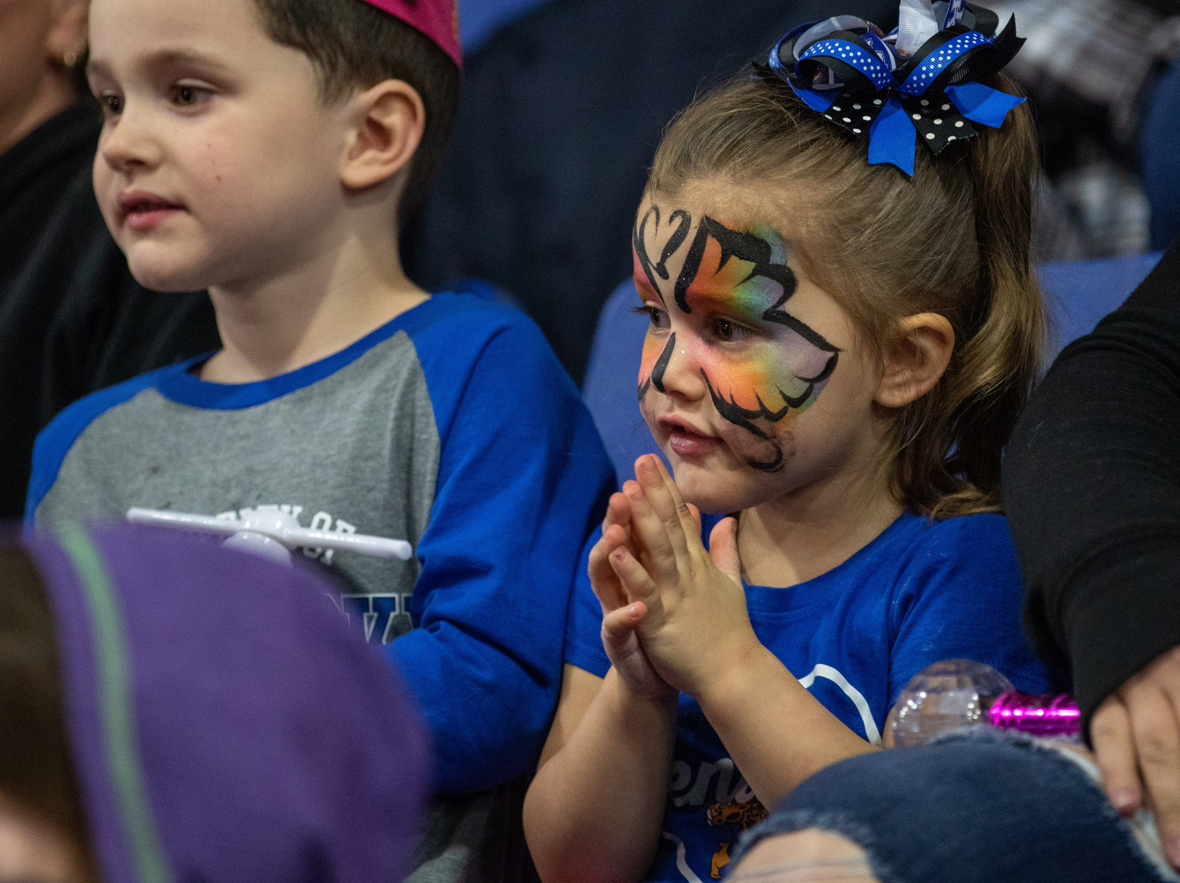 Rainbow colors and a butterfly outline, a little girl's face shows anticipation under her pretty paint, Saturday, Feb. 9, 2019 in Louisville Ky.