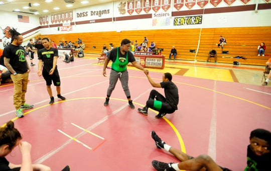 Western wrestler Malasha Lokey helps her warm-up partner, senior Lee'Shion Stroud, to get up.