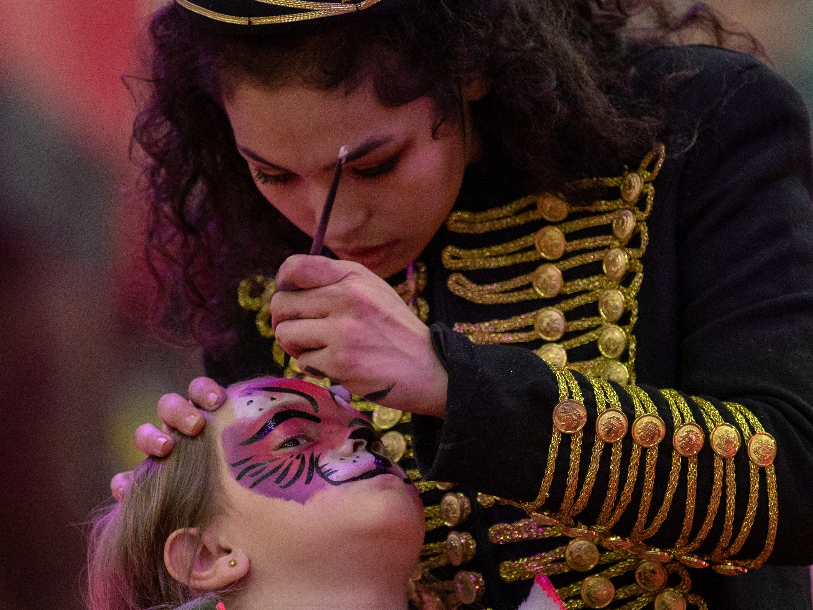 A purple and pink tiger painting comes to life on the face of a young girl before the circus begins, Saturday, Feb. 9, 2019 in Louisville Ky.