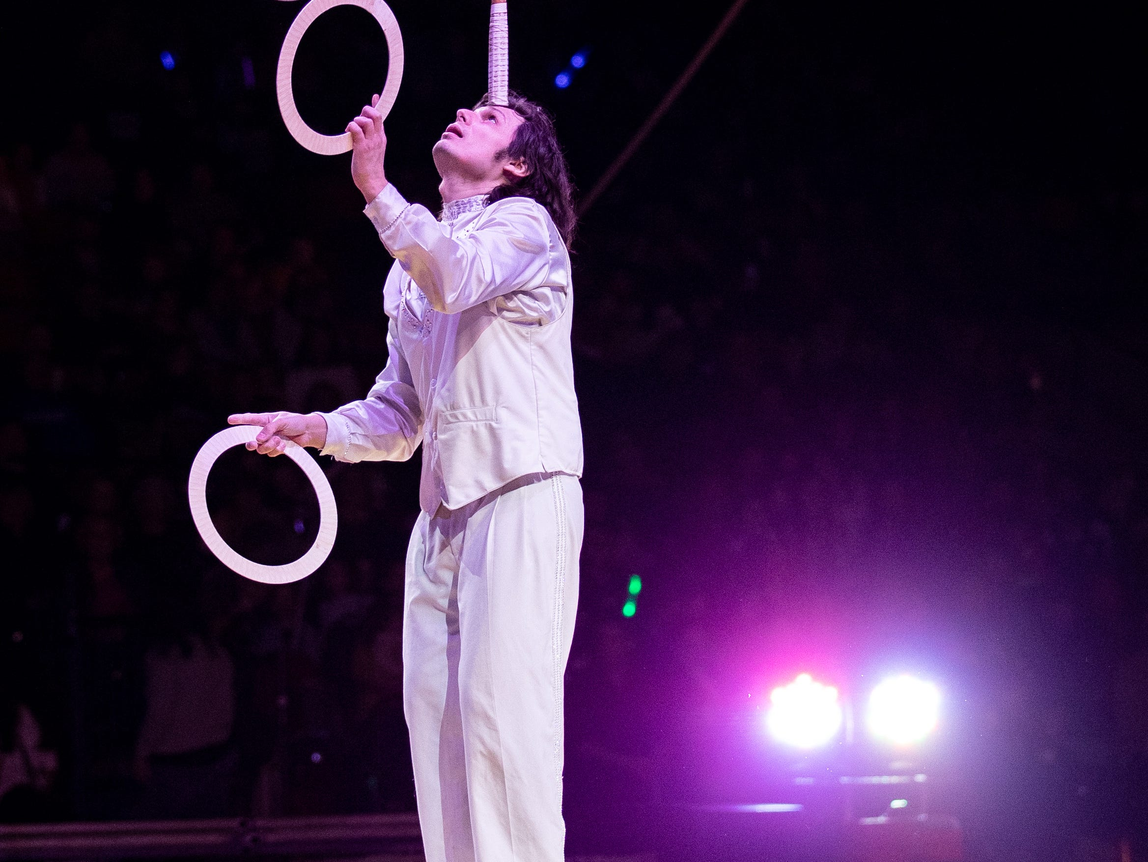 Adding a few more challenges, a juggler balances feet standing on a ball while a racquet and soccer ball teeter on his forehead during the second half of the Kosair Shrine Circus, Saturday, Feb. 9, 2019 in Louisville Ky.