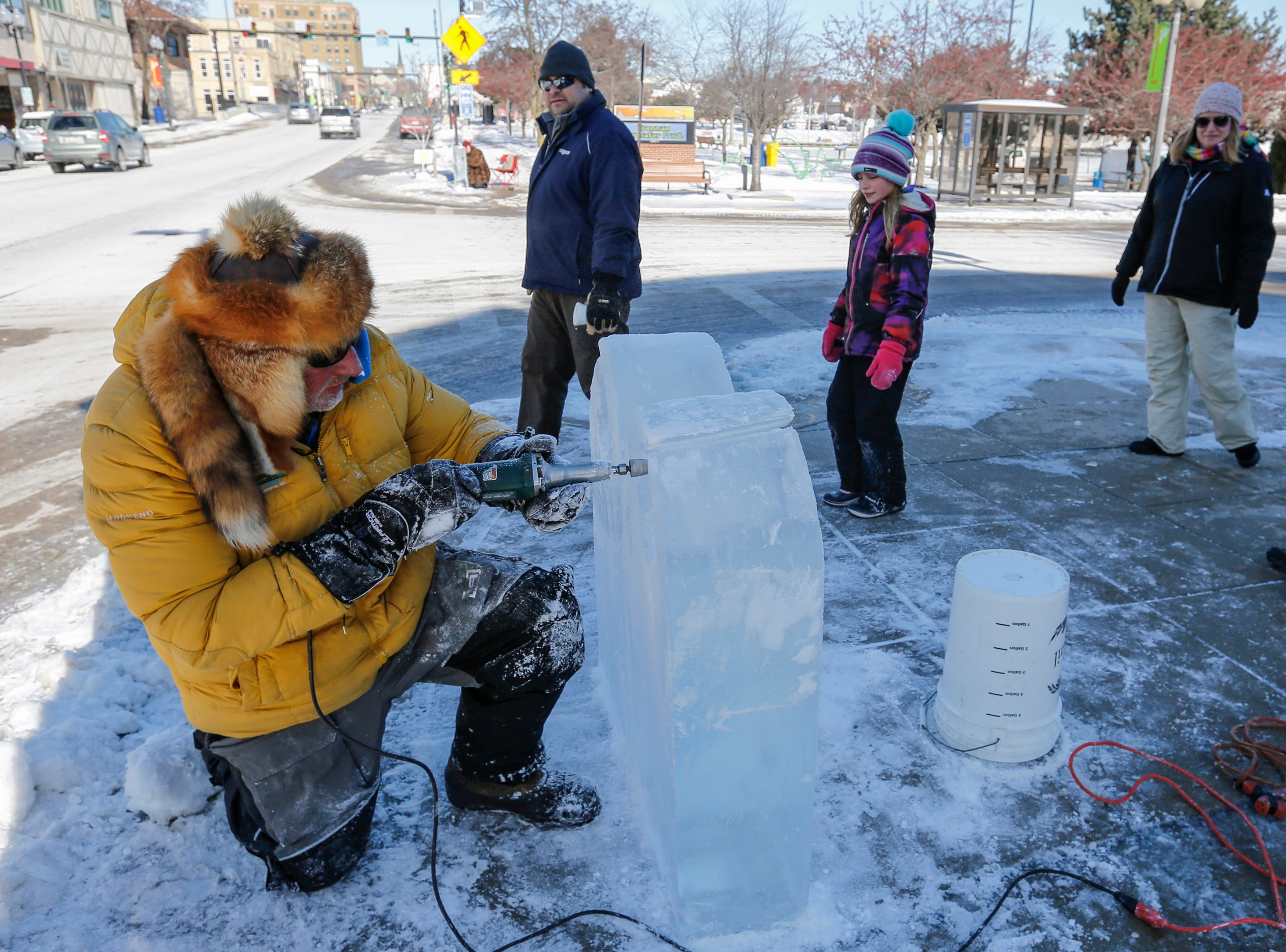 Passersby watch Tom Queoff, of Milwaukee, work on his ice sculpture during Winter Fest Saturday, February 9, 2019, in Manitowoc, Wis. Joshua Clark/USA TODAY NETWORK-Wisconsin