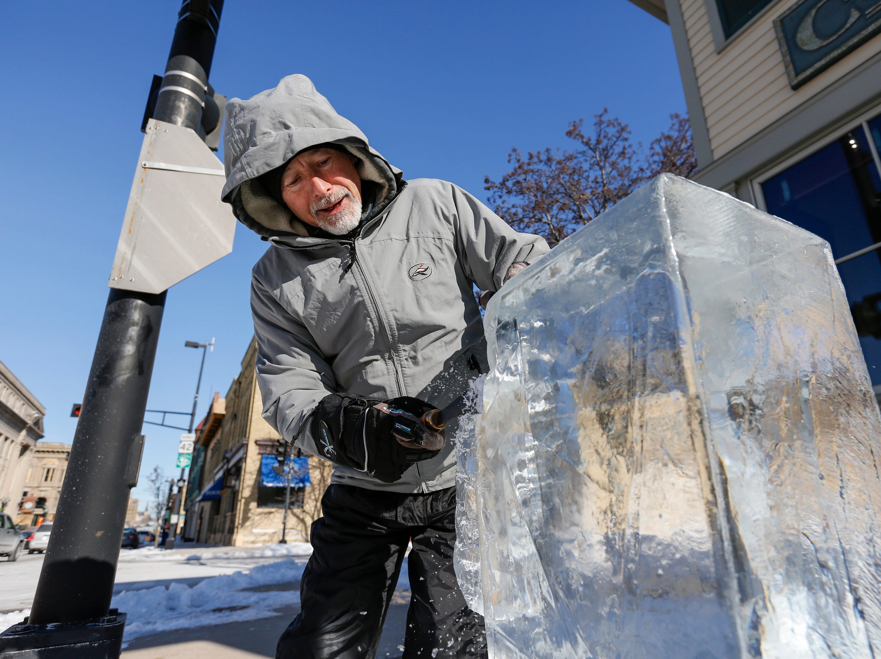 Mike LaBonte works on a sculpture in front of the Courthouse Pub during Winter Fest Saturday, February 9, 2019, in Manitowoc, Wis. Joshua Clark/USA TODAY NETWORK-Wisconsin
