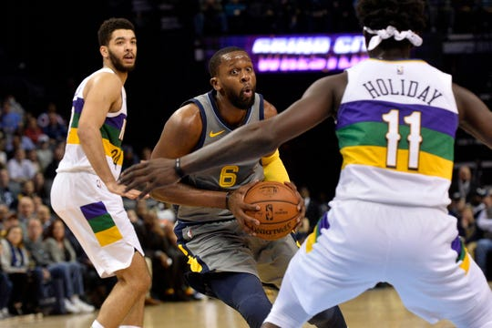 New Grizzlies guard C.J. Miles (6) controls the ball between Pelicans guards Jrue Holiday (11) and Kenrich Williams during the second half Saturday.