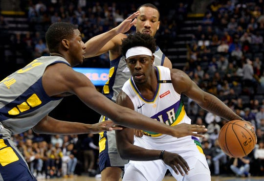 New Orleans Pelicans guard Jrue Holiday, right front, handles the ball against Memphis Grizzlies forward Jaren Jackson Jr., left, and guard Avery Bradley during the first half of an NBA basketball game Saturday, Feb. 9, 2019, in Memphis, Tenn. (AP Photo/Brandon Dill)