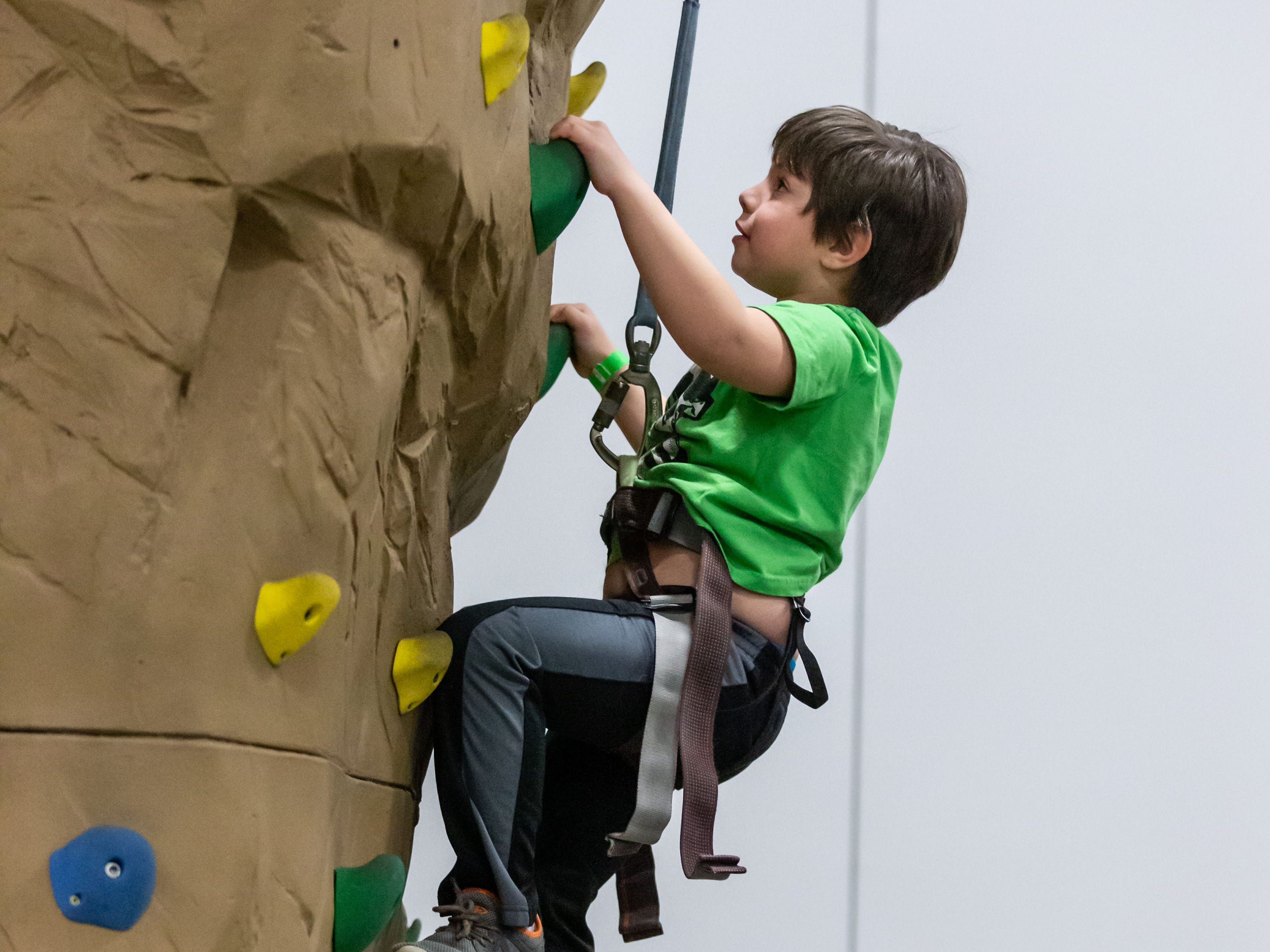 Six-year-old Christopher Moore of Racine makes his way up the Adventure Rock climbing wall during the Milwaukee Kids Expo at State Fair Park in West Allis on Sunday.