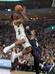 Bucks guard Eric Bledsoe  drives to the basket against Magic guard D.J. Augustin.