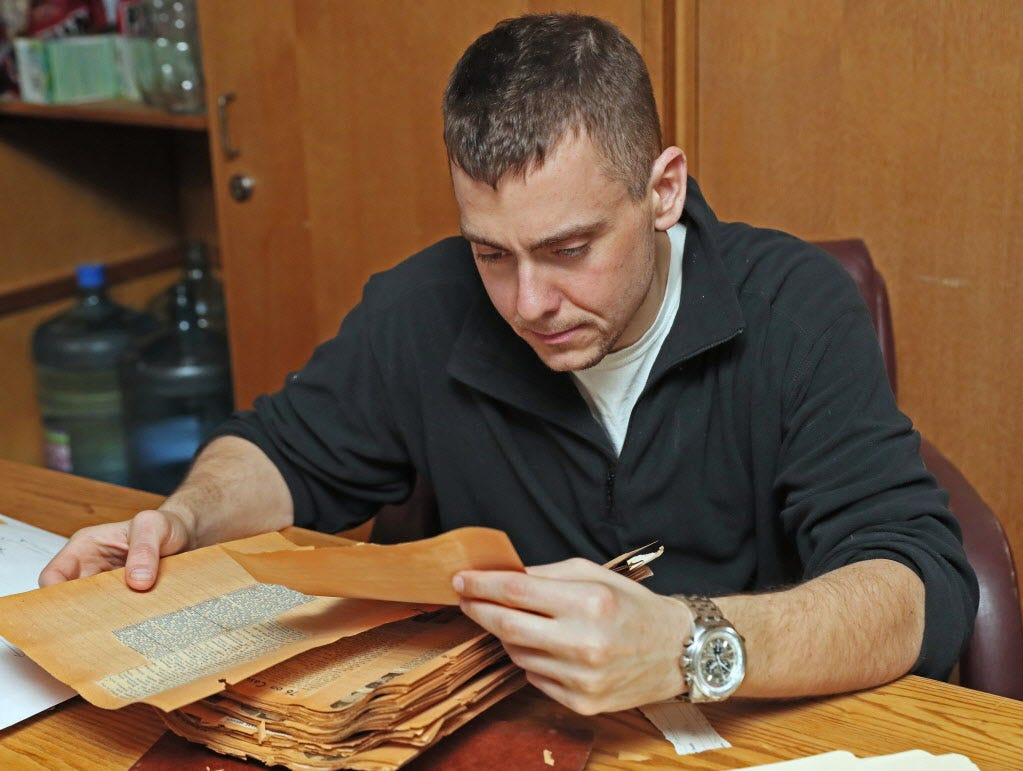 Officer candidate Jason Permann of La Crosse looks through old news clippings about those veterans killed in combat.