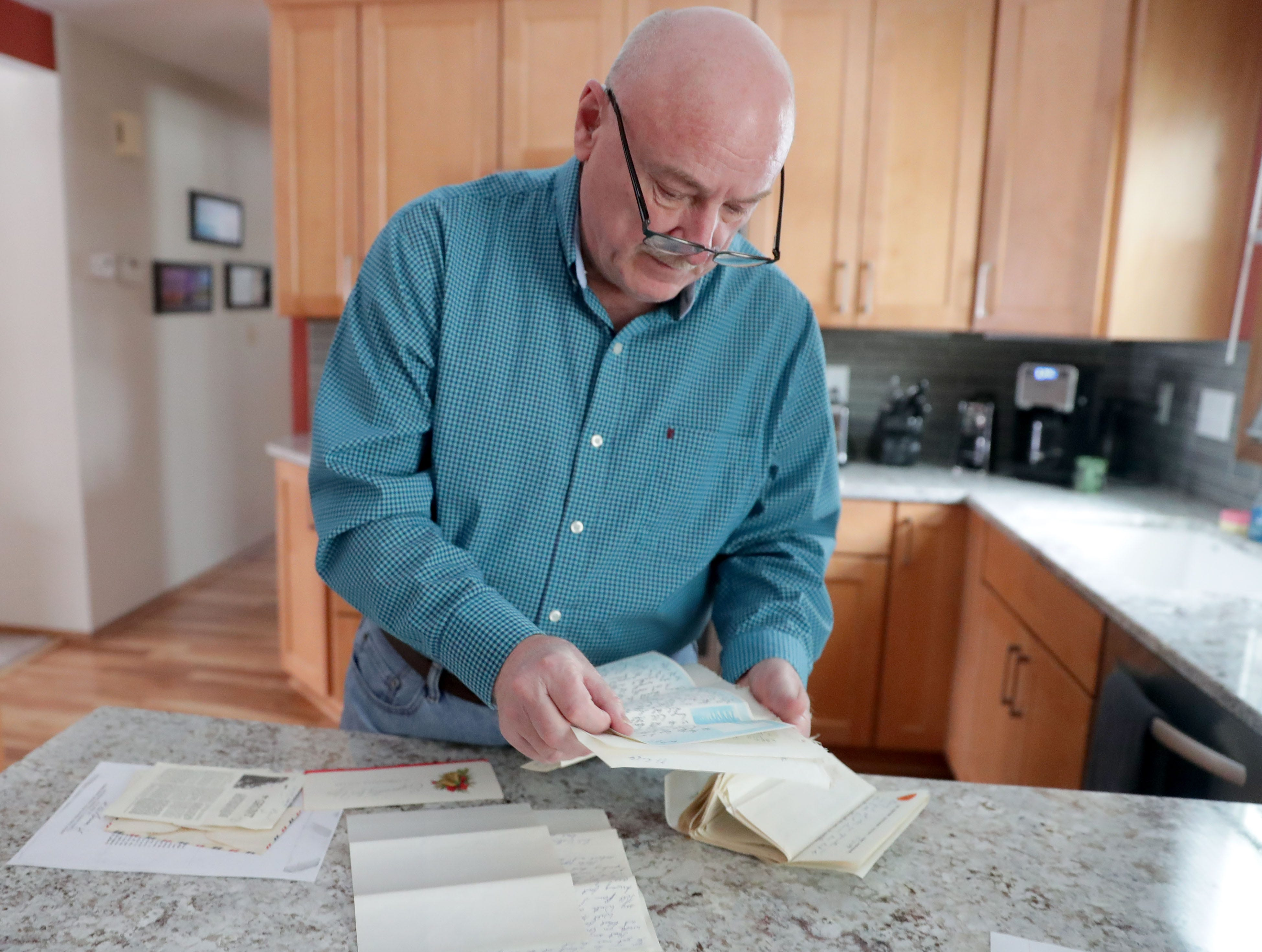 Gary Weckworth looks over letters in his Glendale home sent to him by his childhood friend, Wayne R. Thomas,  while Thomas served in Vietnam.