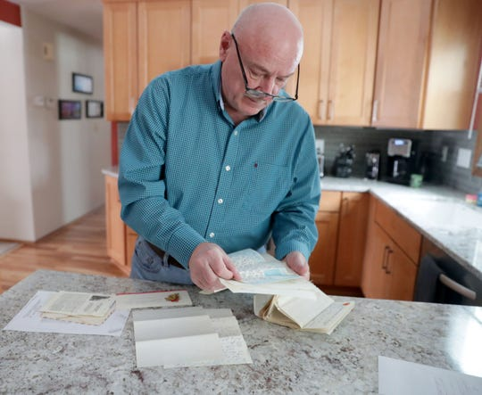 Gary Weckwerth looks over letters in his Glendale home sent to him by his childhood friend, Wayne R. Thomas, while Thomas served in Vietnam.