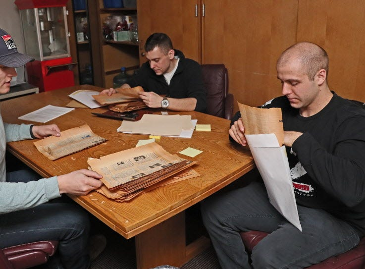 Officer candidates (from left) Zach Lauridsen of Osceola, Jason Permann of La Crosse and Sam Jollie of Madison file and organize old news clippings that brought the sad news of those killed in combat.