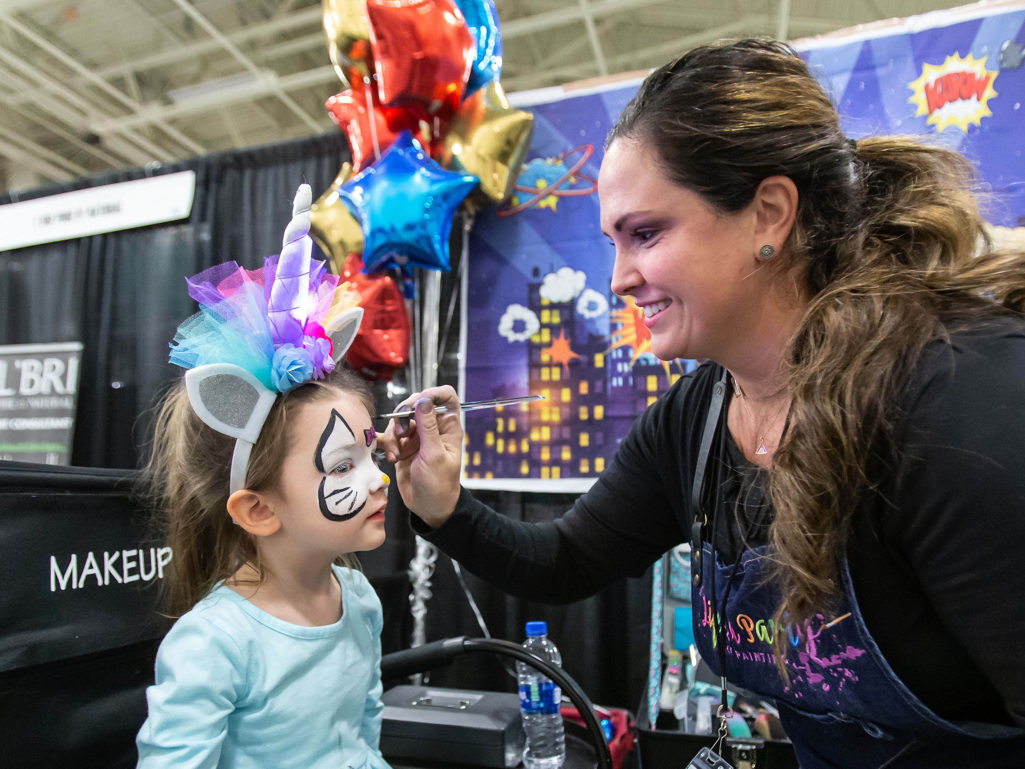 Three-year-old Kaely Krakau of Franklin sits for a face painting by Oconomowoc artist Leea Woolard of Life's a Party - Face Painting during the Milwaukee Kids Expo at State Fair Park in West Allis on Sunday, Feb. 10, 2019. The two-day expo featured bounce houses, a petting zoo, a rock climbing wall, pony rides, caricature paintings, a maze challenge and much more.