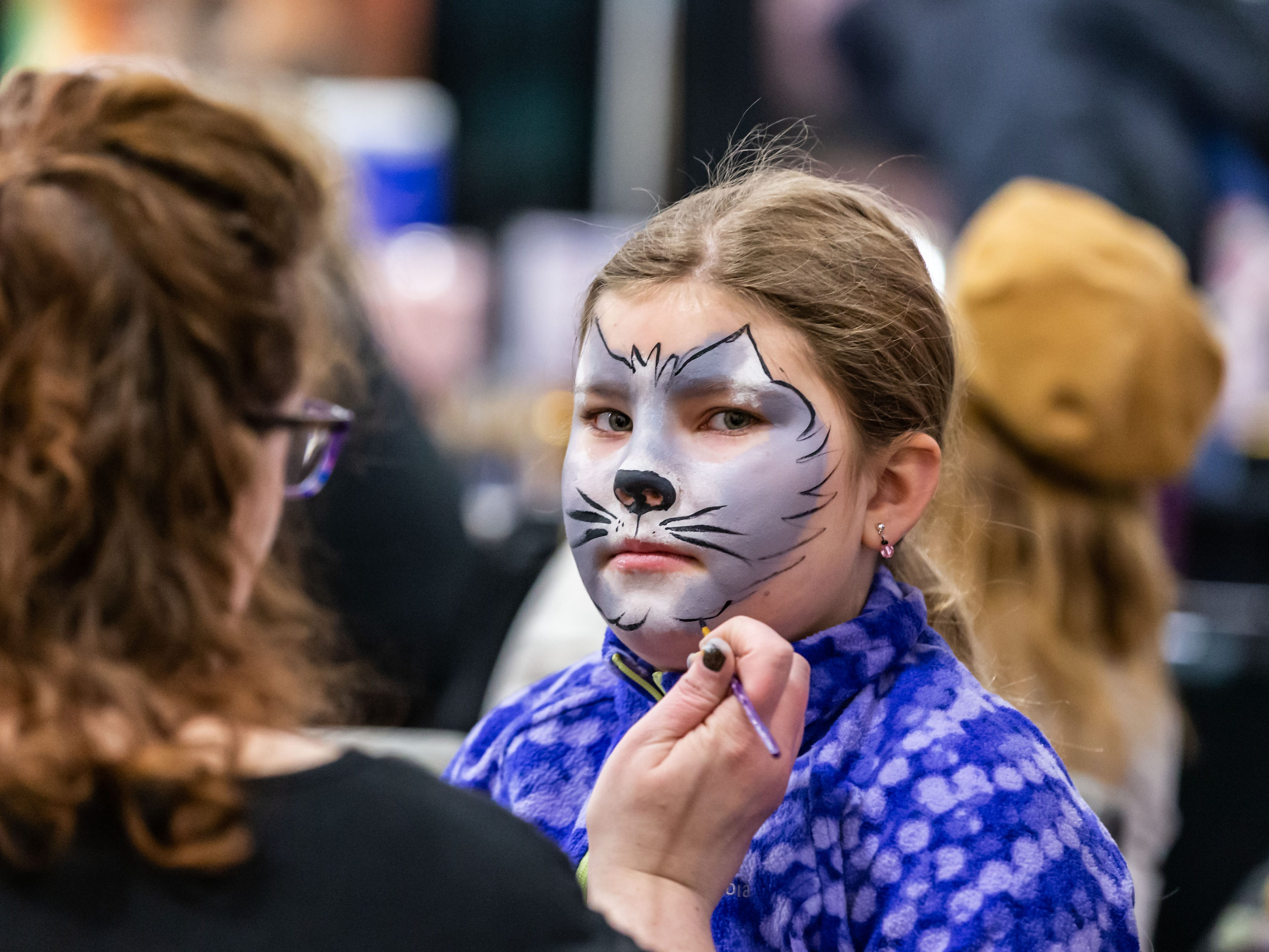 Emma Bruening, 9, of West Bend sits for a face painting by Painted Faces during the Milwaukee Kids Expo at State Fair Park in West Allis on Sunday, Feb. 10, 2019. The two-day expo featured bounce houses, a petting zoo, a rock climbing wall, pony rides, caricature paintings, a maze challenge and much more.