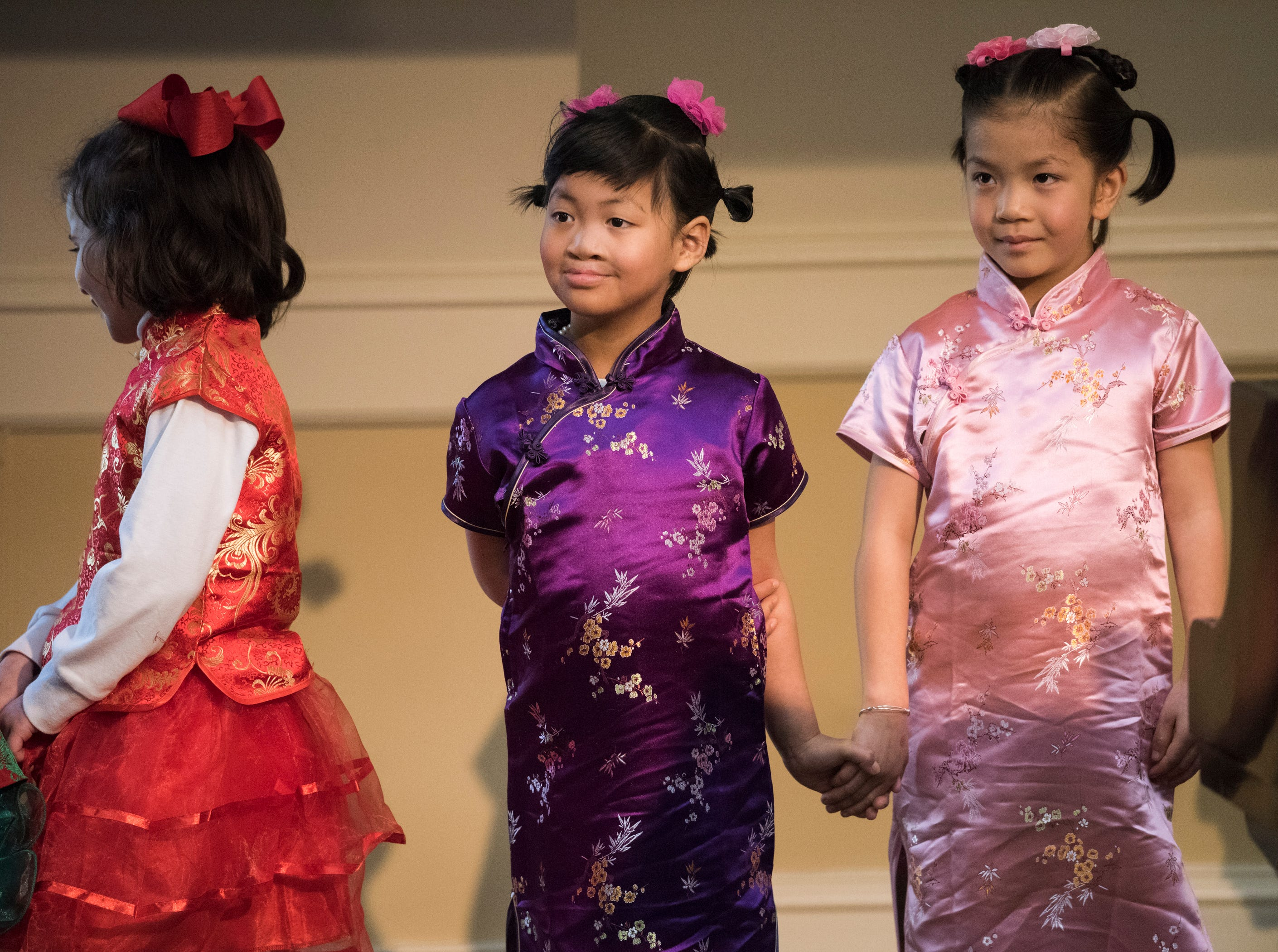 Flora Lin Adams, left, and her sister, Charlotte, both 6, hold hands as they wait to preform during the Central Alabama Association of Chinese 2019 Montgomery Chinese New Year festsival at Frazer Church in Montgomery, Ala., on Saturday, Feb. 9, 2019.