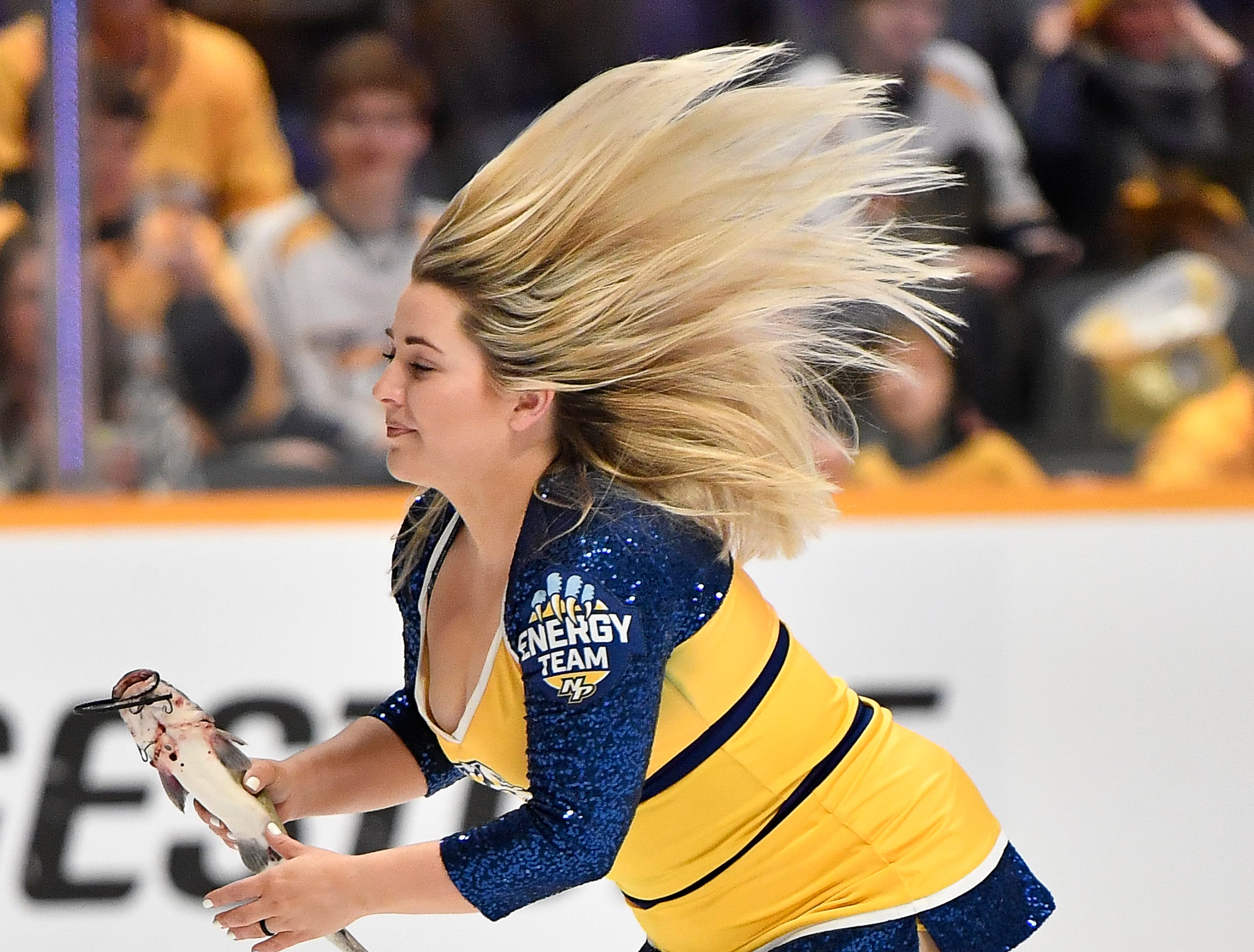 A member of the Predators Energy Team picks up a catfish form the ice before their game against the Blues at Bridgestone Arena Sunday Feb. 10, 2019 in Nashville, Tenn.