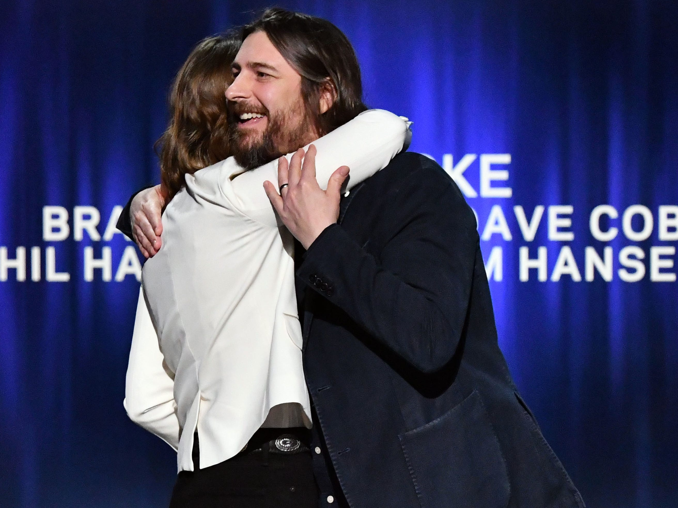 Brandi Carlile embraces Dave Cobb as she accepts the award for Best American Roots Song for The Joke at the GRAMMY Awards Premiere Ceremony at the Microsoft Theater in Los Angeles, Calif.