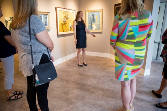 Juliana Meek, center, gives members of Tall Friends of Southwest Florida a tour of Harmon-Meek Gallery during a group outing in Naples on Sunday, Feb. 10, 2019. Meek, who is 5-foot-11, enjoys being part of the social club because, she says, it's nice to be able to stand up tall around people her height and she doesn't have to bend over in photos.