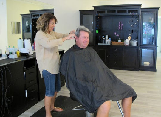Lexy Verderamo cuts the hair of Dr. Bill Carey, a client at the new Lakewood Barber Shop in East Naples.