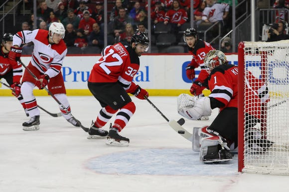 Feb 10, 2019; Newark, NJ, USA; New Jersey Devils goaltender Keith Kinkaid (1) makes a save on Carolina Hurricanes right wing Saku Maenalanen (8) during the first period at Prudential Center.