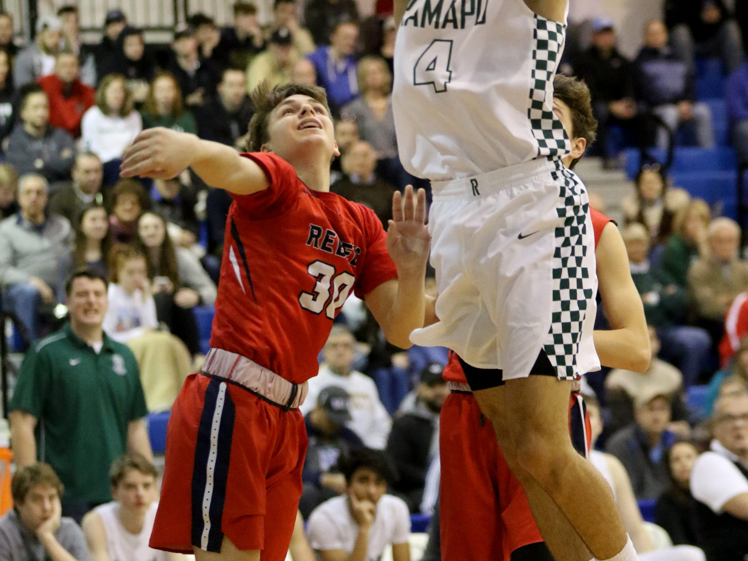 Max Pernetti, of Ramapo, goes up for a basket against Ryan Cassels, of Saddle River Day.  The Raiders won the Bergen County Jamboree game, 78-60. Sunday, February 10, 2019