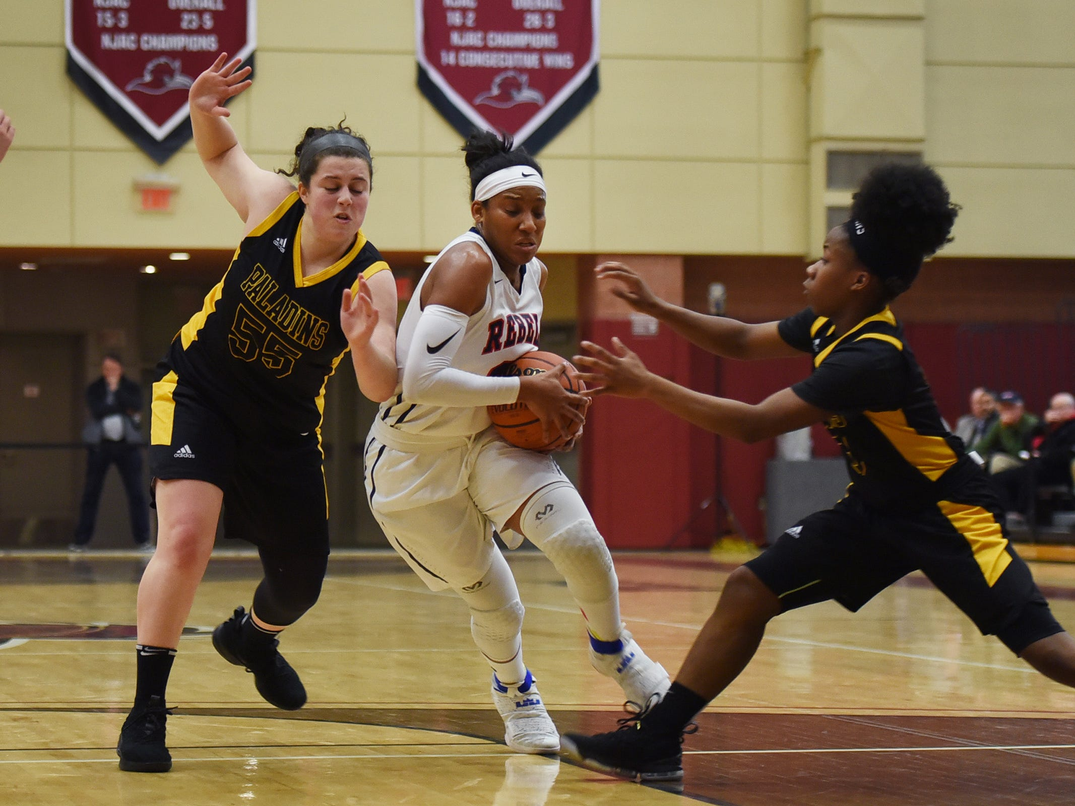Sydnei Caldwell (no.21) of Saddle River Day makes her way past Julianna Kascic (no.55) and Janel Moore (no.3) of Paramus Catholic in the first half during the 2019 Bergen County girls basketball championship semifinal at Ramapo College in Mahwah on 02/10/19.
