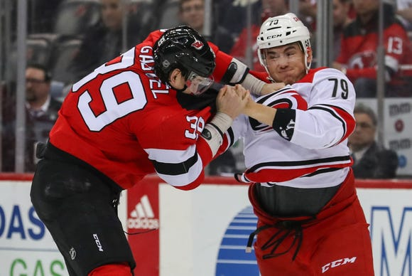 Feb 10, 2019; Newark, NJ, USA; Carolina Hurricanes left wing Micheal Ferland (79) and New Jersey Devils right wing Kurtis Gabriel (39) fight during the first period at Prudential Center.