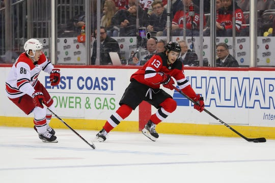 Feb 10, 2019; Newark, NJ, USA; New Jersey Devils center Nico Hischier (13) skates with the puck past Carolina Hurricanes left wing Teuvo Teravainen (86) during the second period at Prudential Center.