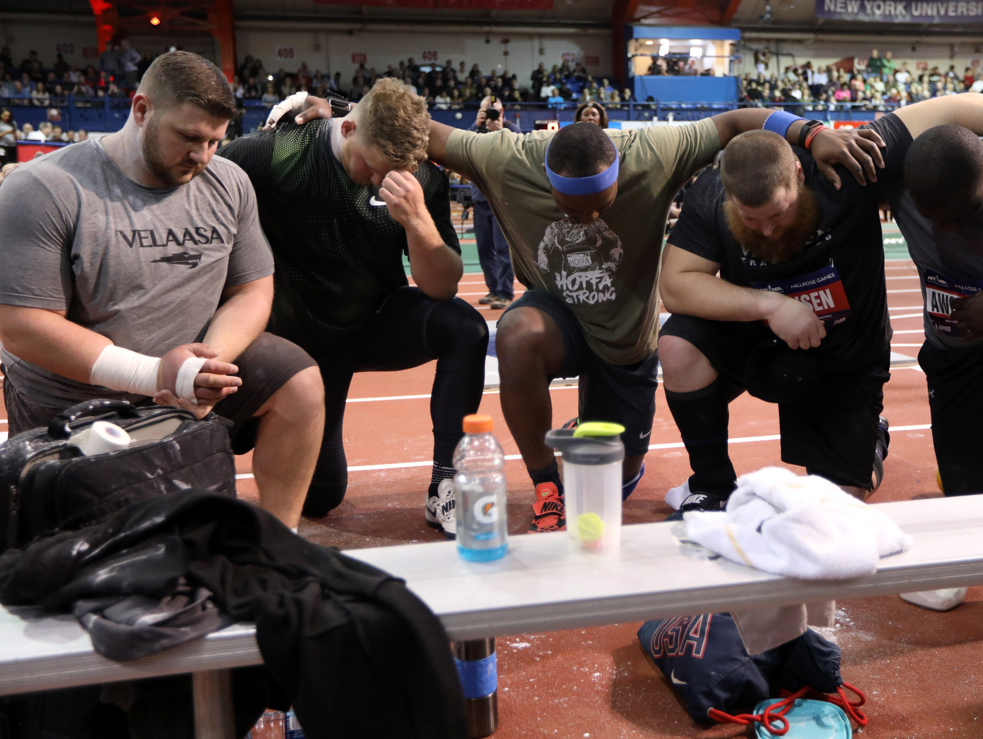 Shot put competitors pray for Kemoy Campbell (not shown), Campbell was running as the rabbit in the 3000 meter race. At one point he stepped off the track and collapsed.  He was taken away in a stretcher. Saturday, February 9, 2019