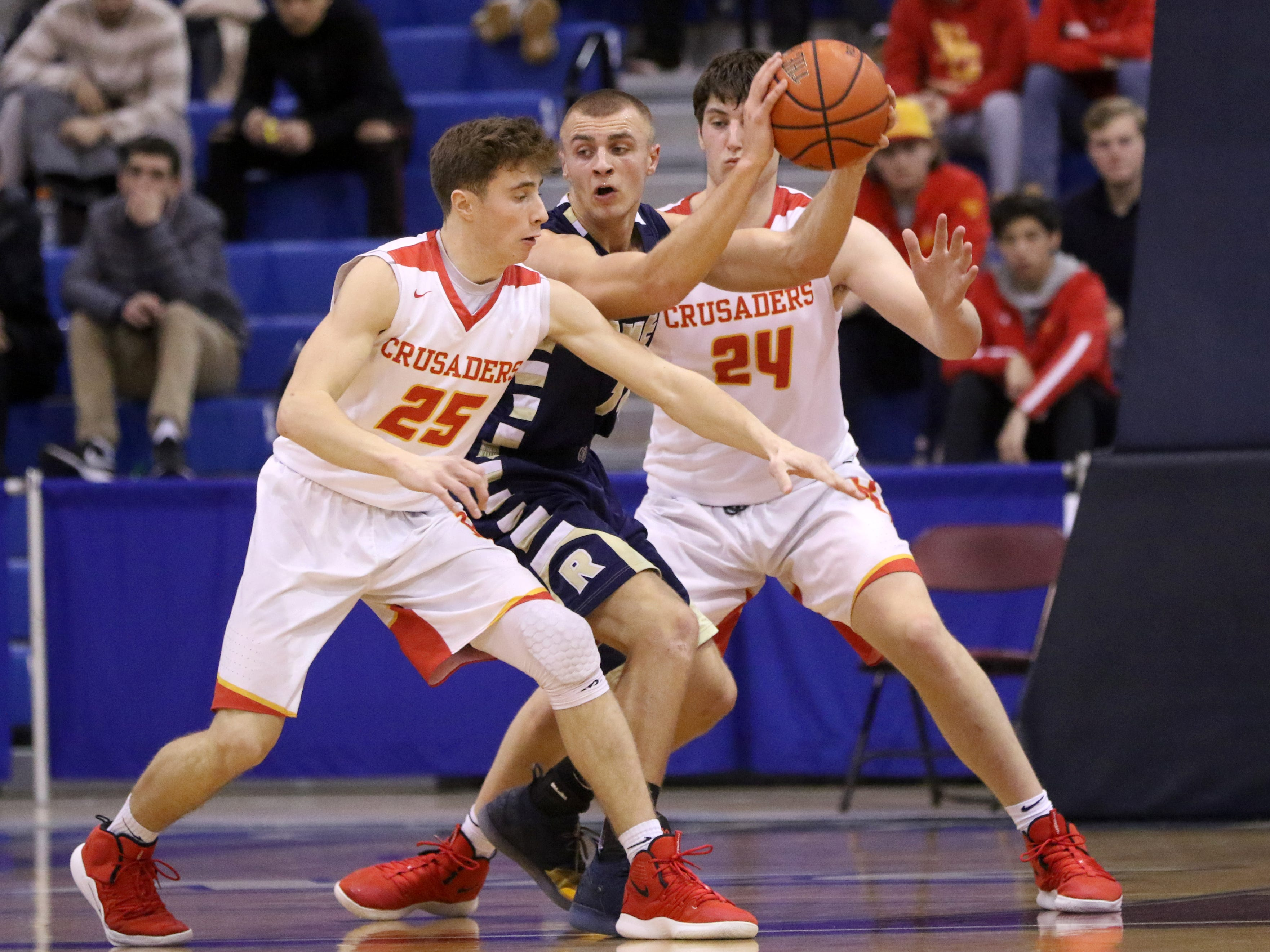 Kevin Foelsch, of Ramsey, tries to get rid of the ball as Doug Edert (25) and Matt Zona (24), both of Bergen Catholic, surround him.  Sunday, February 10, 2019