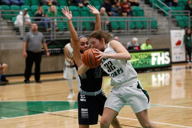 Farmington's Jordan Vasquez pushes her way toward the basket against La Cueva's Rachael Hathoot during Saturday's District 2-5A game at Scorpion Arena. Piedra Vista, West Mesa, FHS and LC are within one or two games of each other in the district title race.