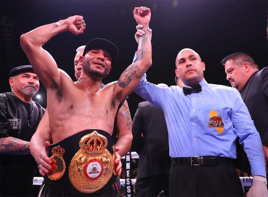 Andrew Cancio raises his arms in victory as the WBA super featherweight world title is wrapped around his waist iun February. Cancio retained his title Friday, June 21, 2019.