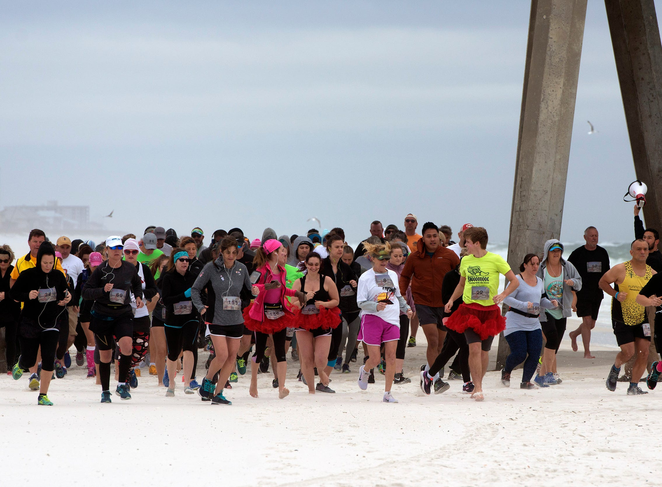 Runners make their way along Pensacola Beach Sunday, February 10, 2019 during the Kiss Me 5k- 10k.