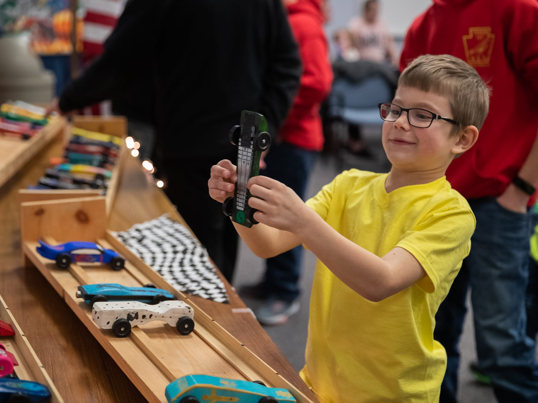 A cub scout looks at his pinewood car during the cub scouts pack 127 Pinewood Derby event at Lincoln Intermediate Unit 12, Sunday, Feb. 10 in New Oxford. The scouts had a month to design their custom pinewood cars to race in the event.