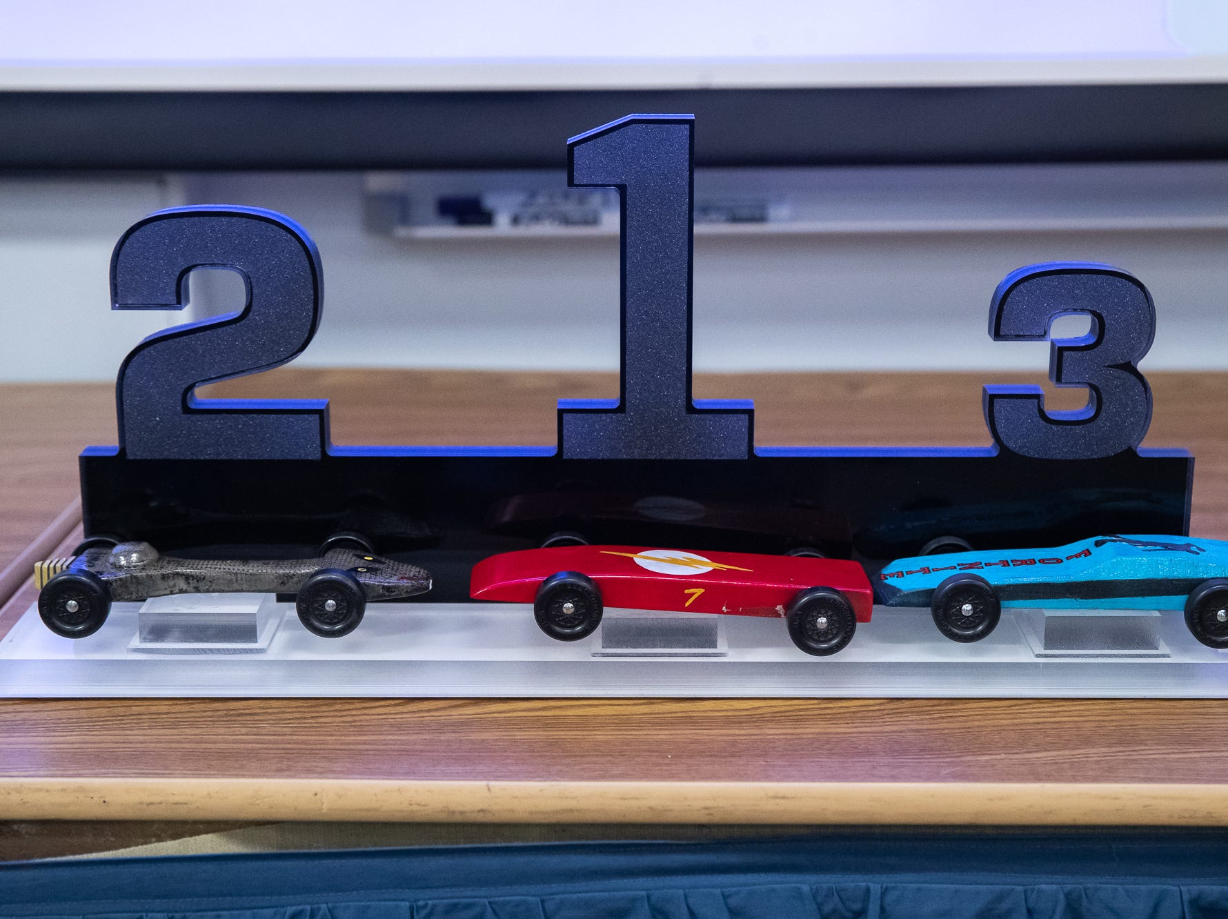 The top three cars sit upon a trophy during the cub scouts pack 127 Pinewood Derby event at Lincoln Intermediate Unit 12, Sunday, Feb. 10 in New Oxford. The scouts had a month to design their custom pinewood cars to race in the event.