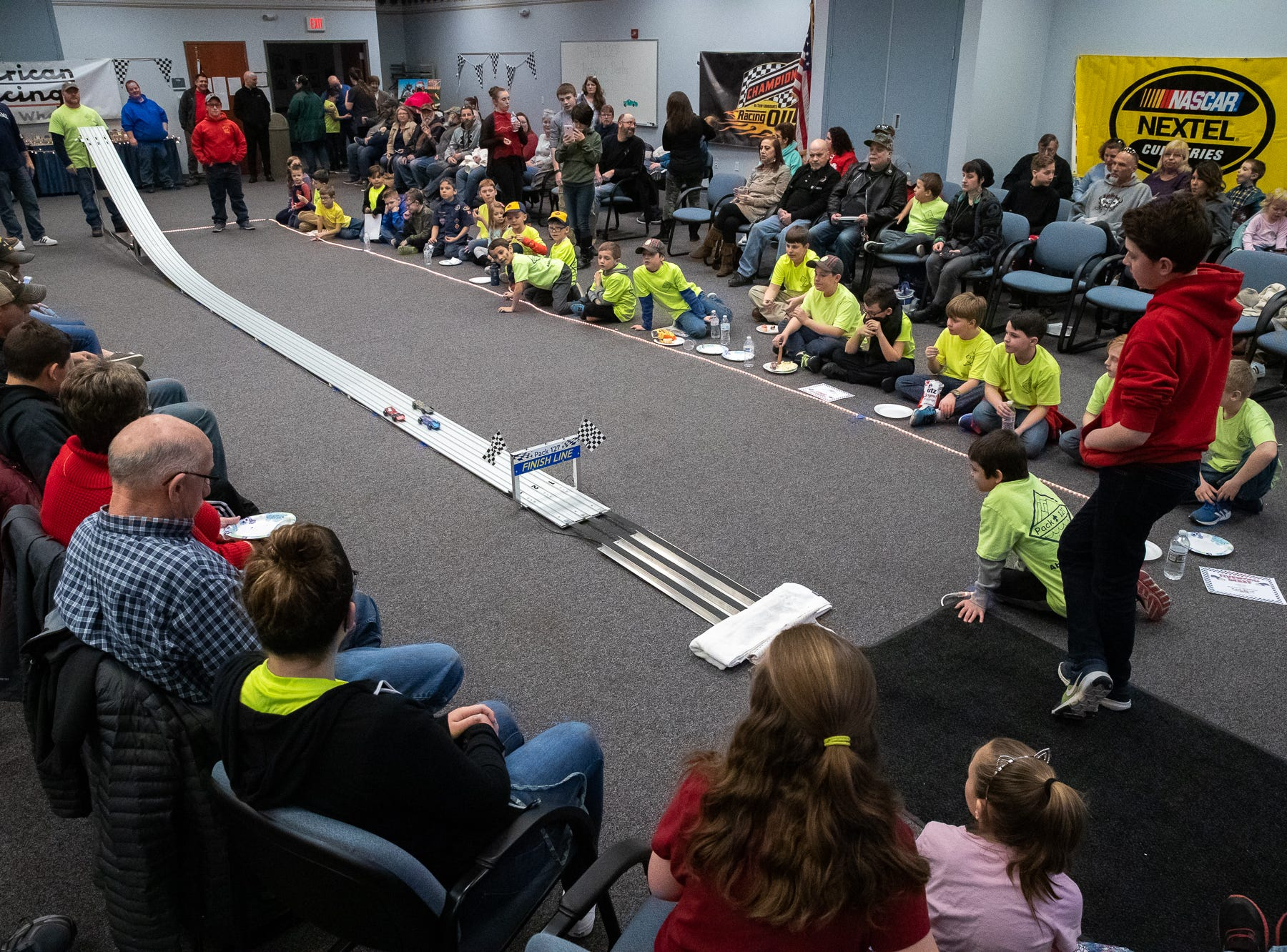 Spectators watch cars race during the cub scouts pack 127 Pinewood Derby event at Lincoln Intermediate Unit 12, Sunday, Feb. 10 in New Oxford. The scouts had a month to design their custom pinewood cars to race in the event.