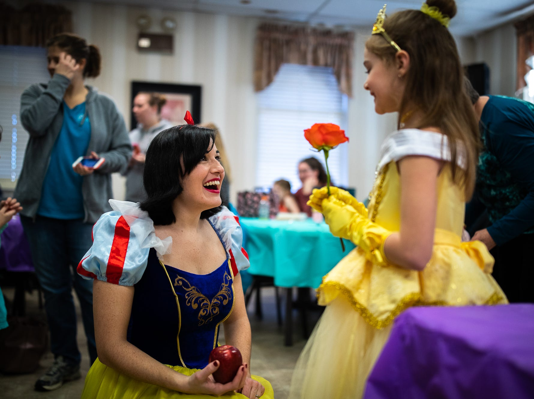 Princess Snow White smiles at Skylar, 6, dressed as princess Belle, during a princess teatime hosted by the Black Rose Rollers, Saturday, Feb. 9, 2019, at the Hanover YWCA.