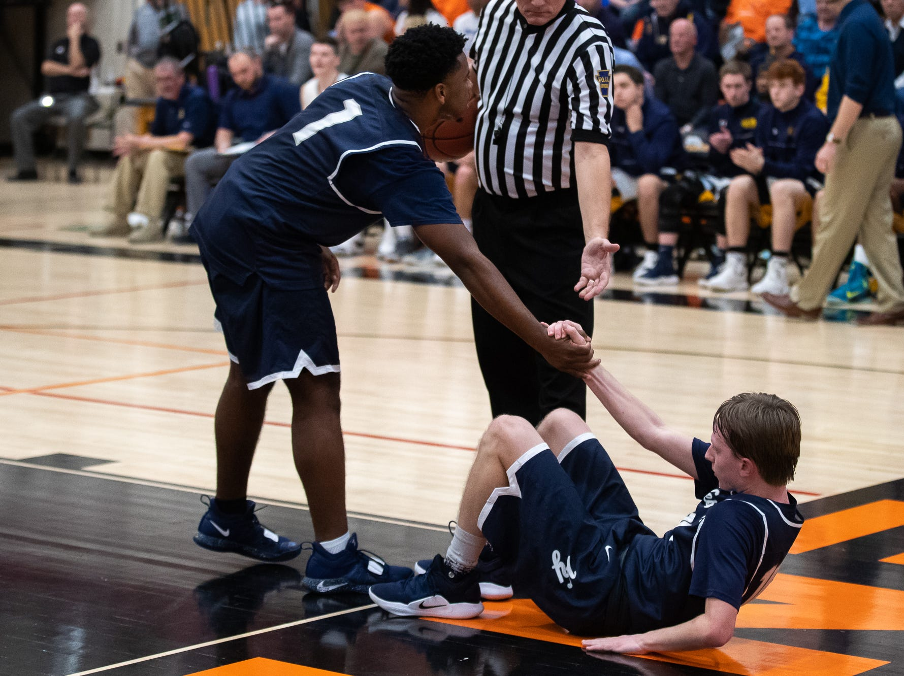 West York's Kelvin Matthews (1) helps up West York's Corey Wise (10) after he fell during the second half of the YAIAA boys' basketball quarterfinals between Littlestown and West York, Saturday, Feb. 9, 2019, at Central York High School. The Littlestown Bolts defeated the West York Bulldogs 73-63.