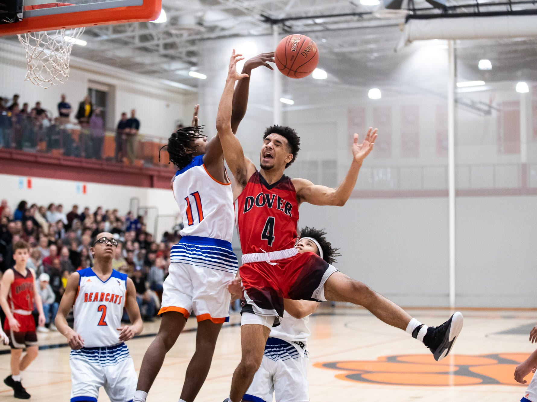 Dover's Keith Davis (4) goes up against York High's Branden X. Mutunga (11) during the first half of a YAIAA quarterfinal between York High and Dover, Saturday, Feb. 9, 2019, at Central York High School. West York led Dover 48-35 at the half.