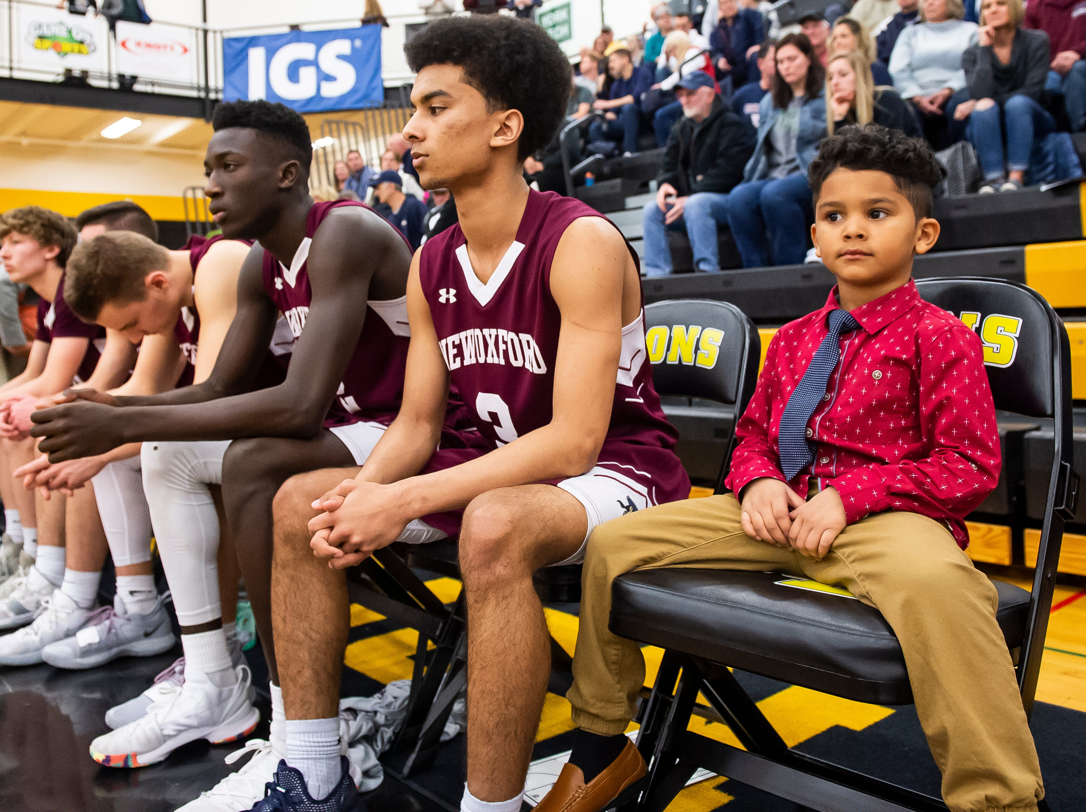 Gabriel Edwards sits on the bench along with New Oxford's starters prior a YAIAA quarterfinal game against Eastern York at Red Lion High School Saturday, February 9, 2019. Gabriel is the son of JV coach Nathan Edwards.