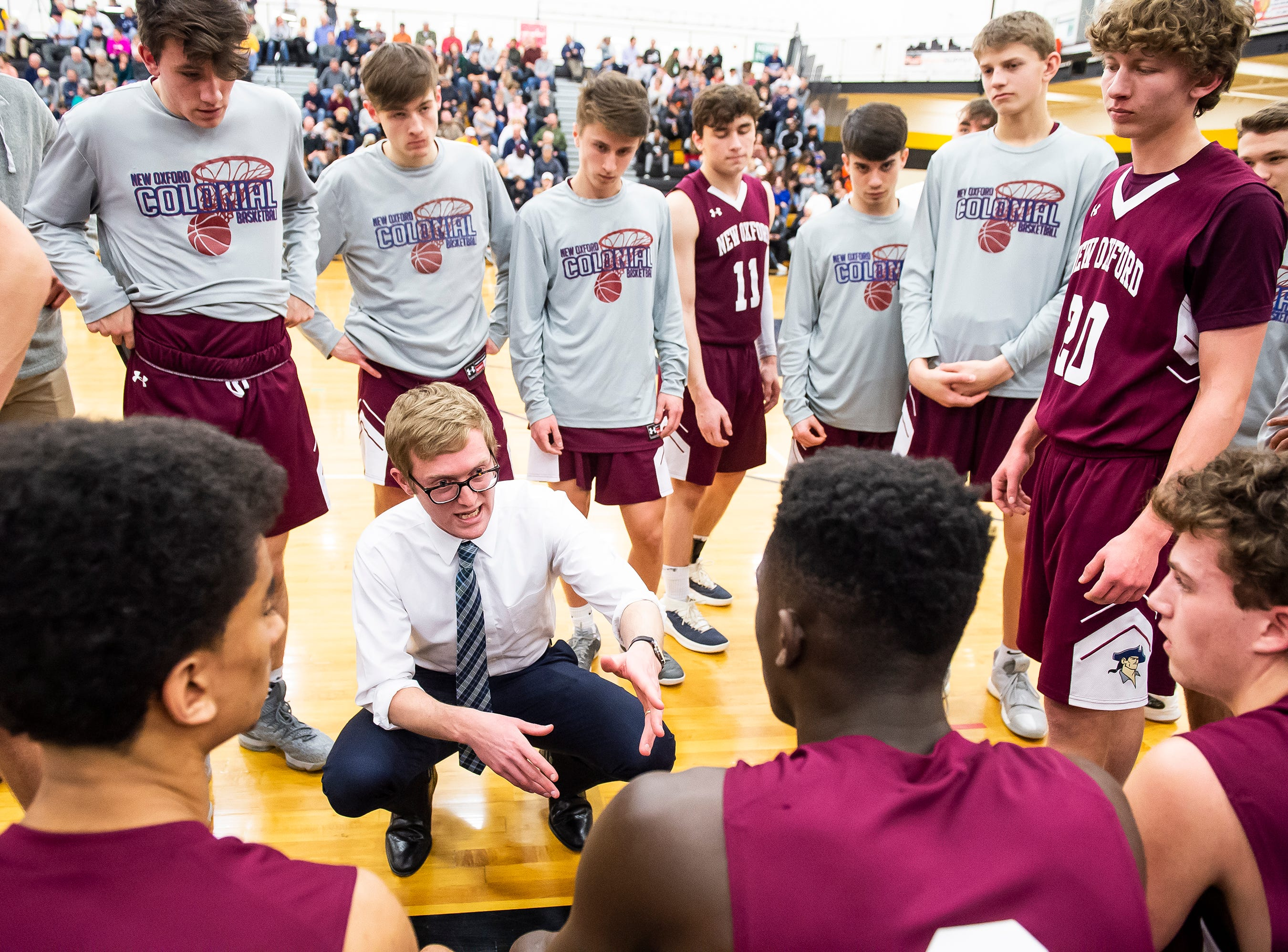 "New Oxford head coach Sean Bair talks with his team before the start of the second quarter against Eastern York in a YAIAA quarterfinal game at Red Lion High School Saturday, February 9, 2019. ""We haven't seen a team that plays that hard and that physical all year,"" Bair said of Eastern York after the Colonials' 54-44 victory."
