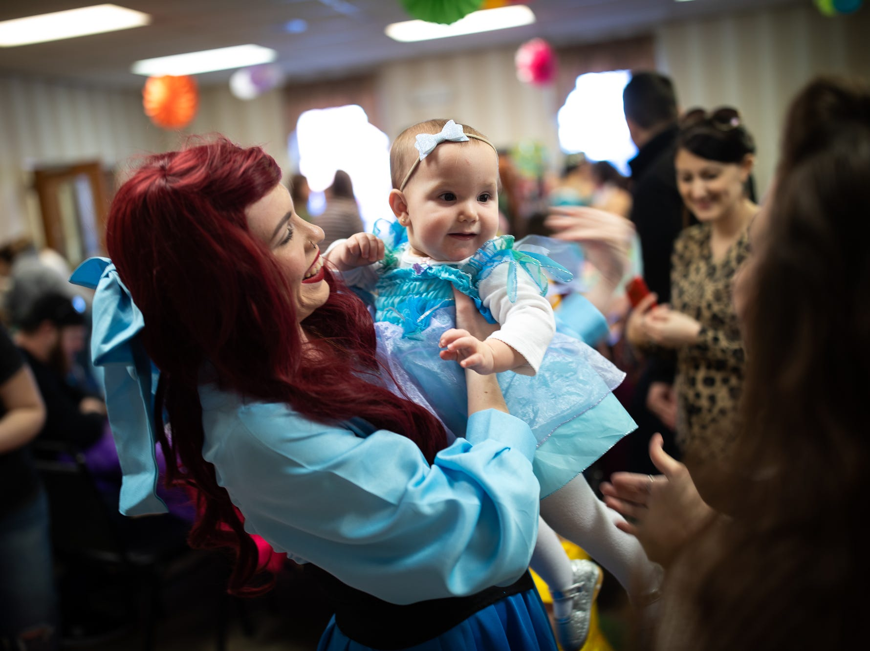 Princess Ariel picks up Cheyenne, 16 months, during a princess teatime hosted by the Black Rose Rollers, Saturday, Feb. 9, 2019, at the Hanover YWCA.